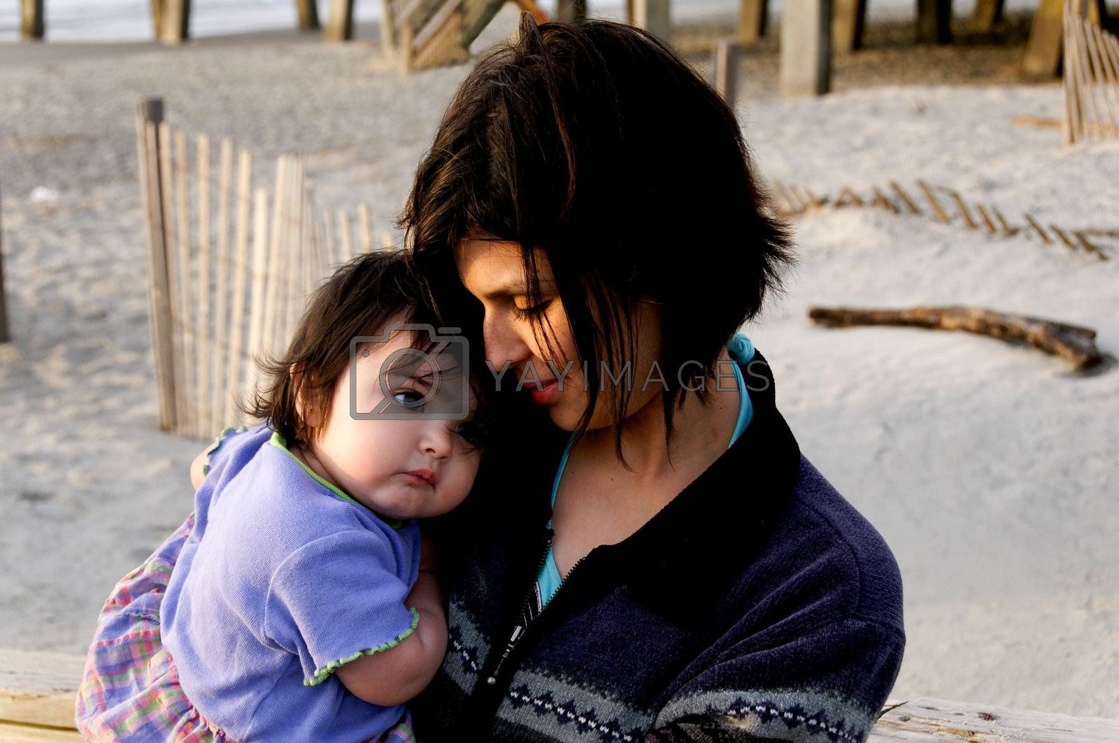 A hispanic mother holding her baby at the beach.
