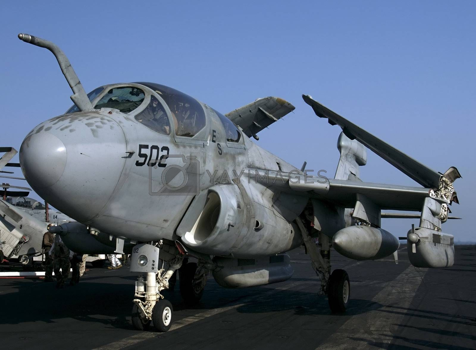 An EA-6B Prowler Electronic Attack aircraft taxies on an aircraft carrier