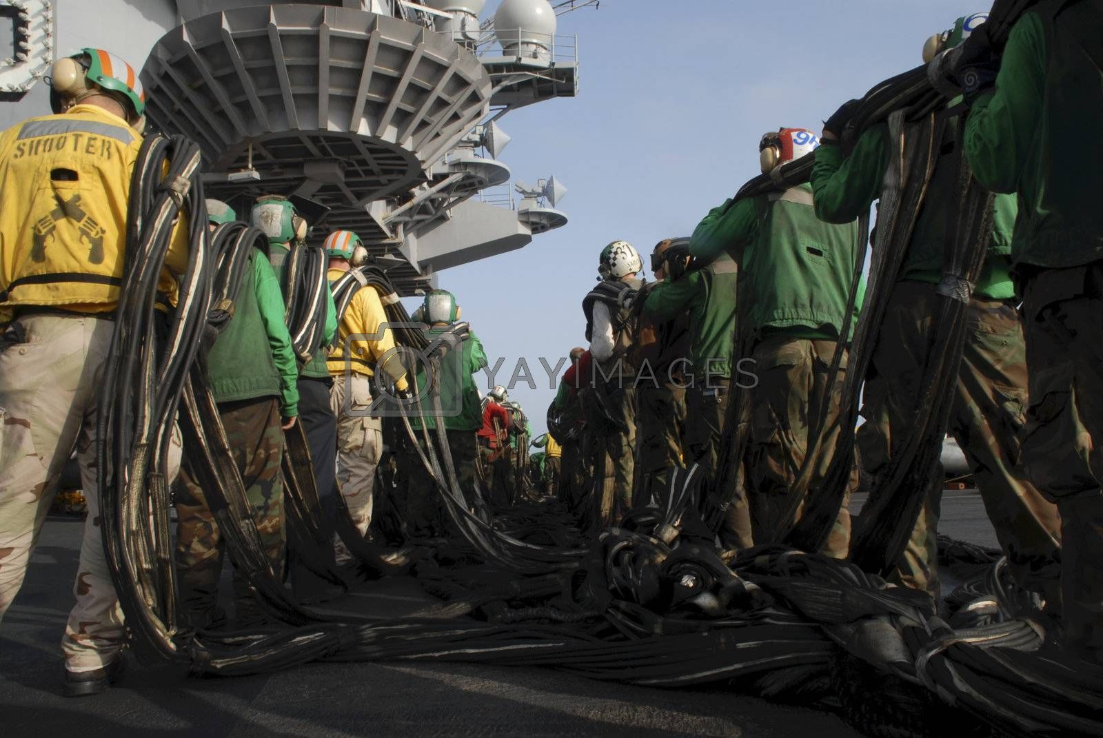 Sailors on board an aircraft carrier set up an emergency barricade