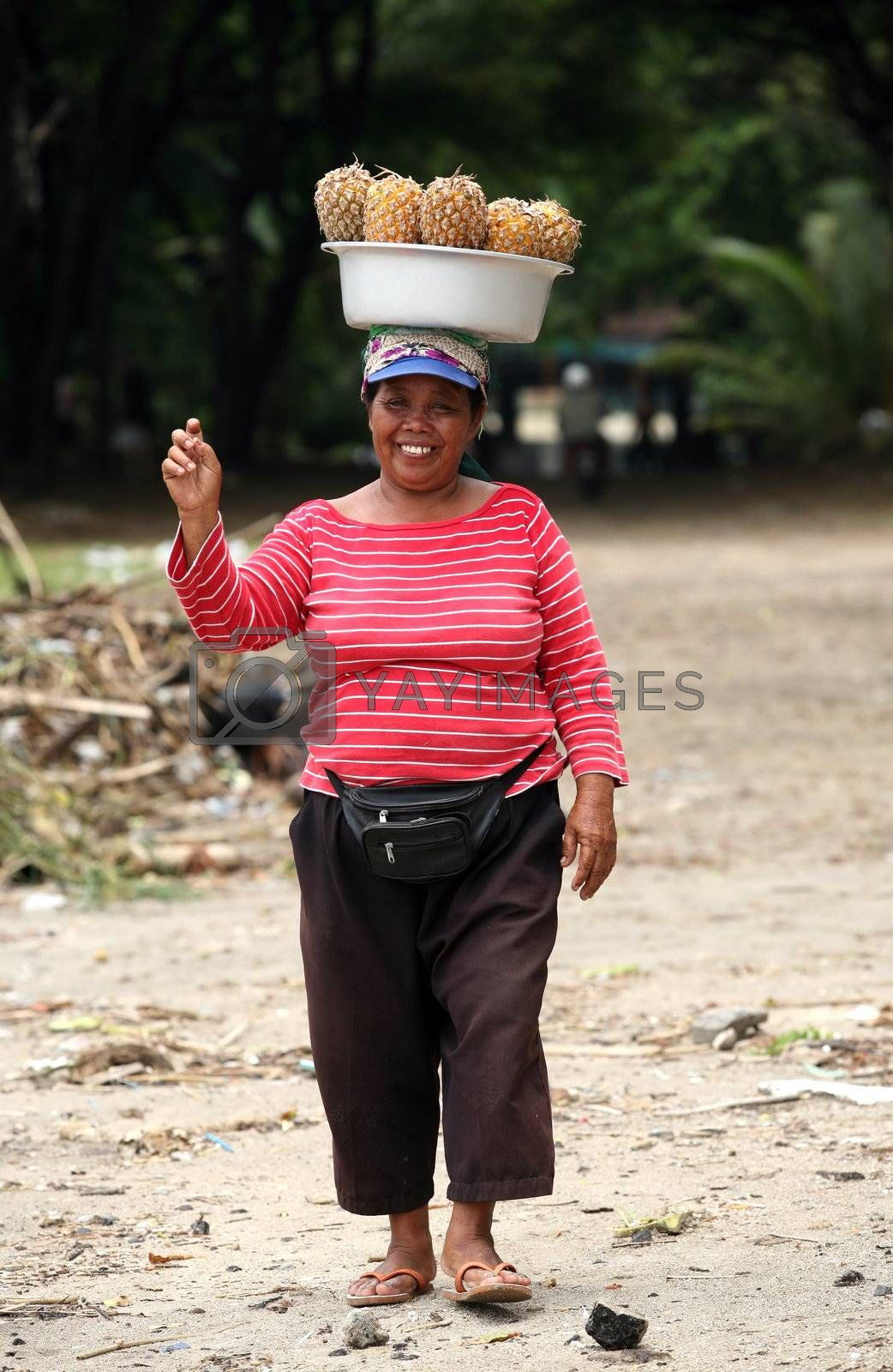 Saleswoman of  tropical fruits on a coast of ocean. Bali. Indonesia