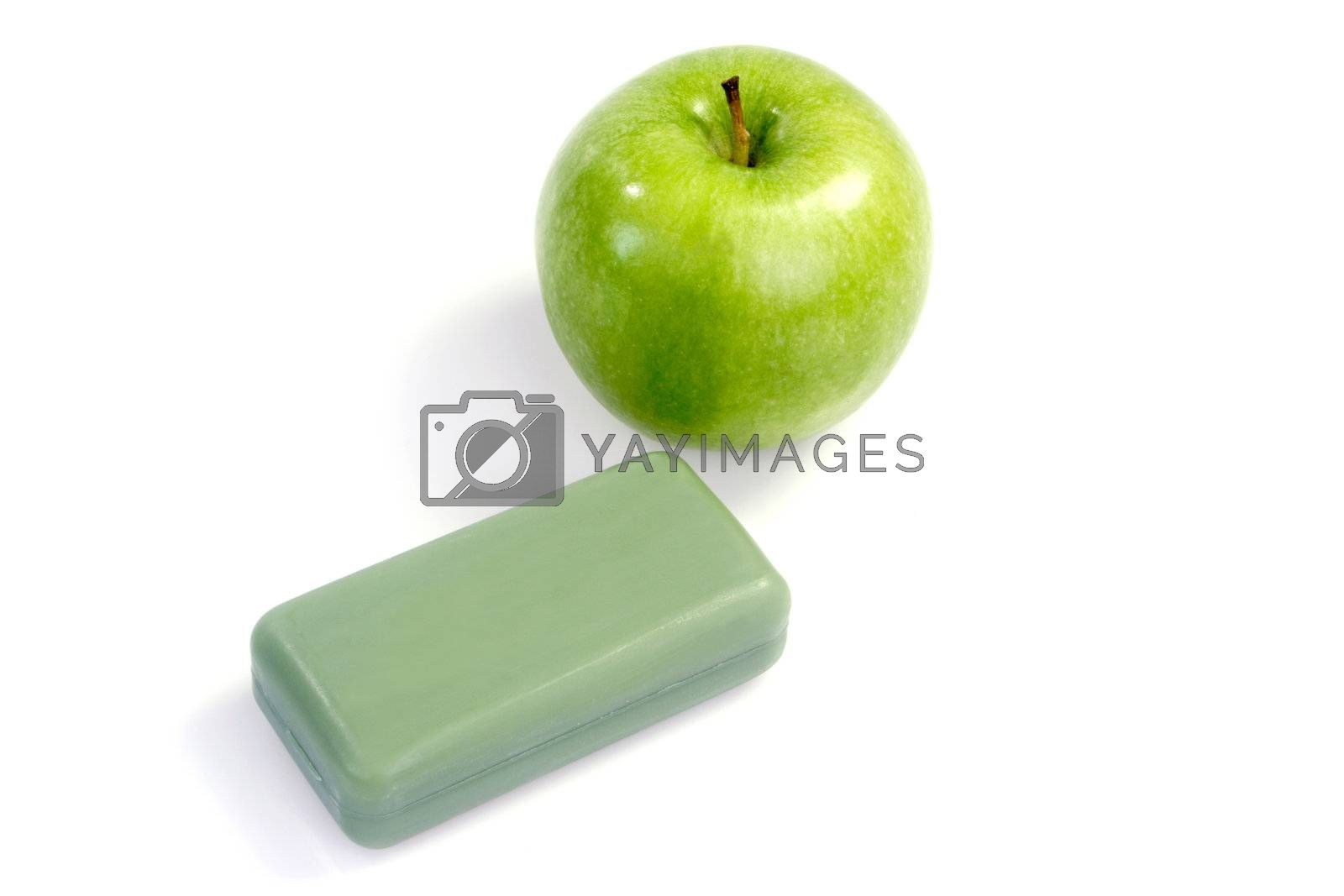 Bar of green soap with a green apple on white background