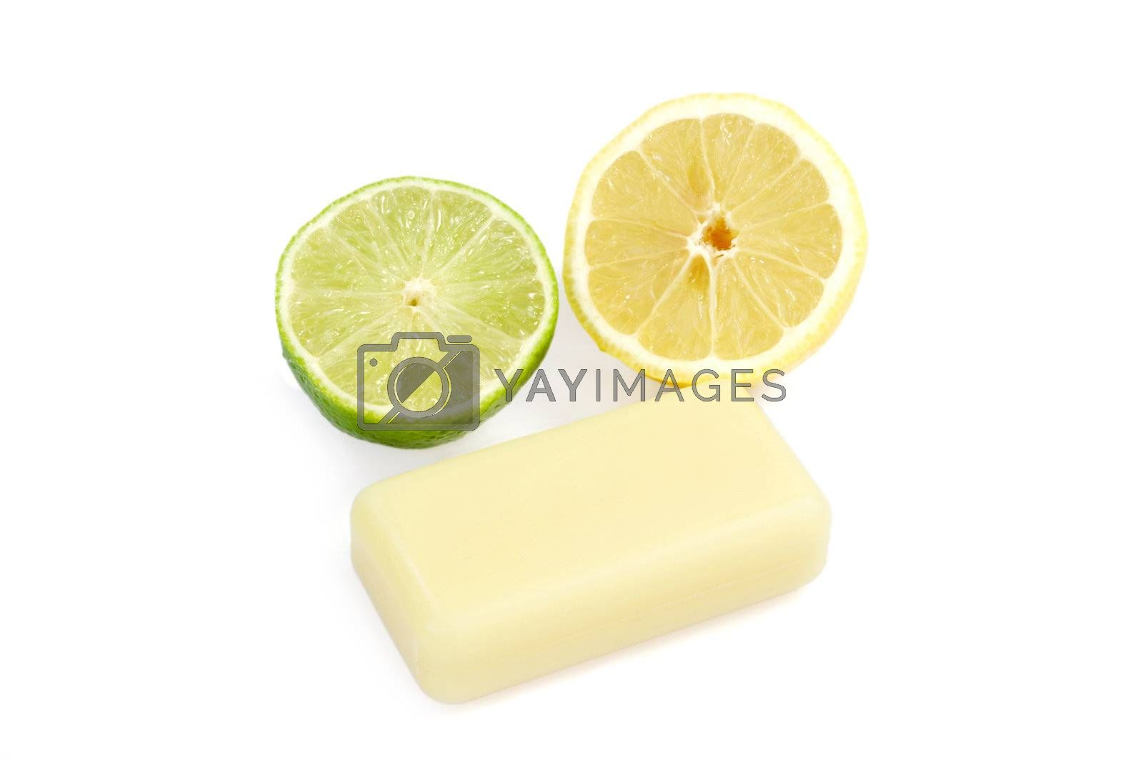 Bar of yellow soap with lemon and lime on white background