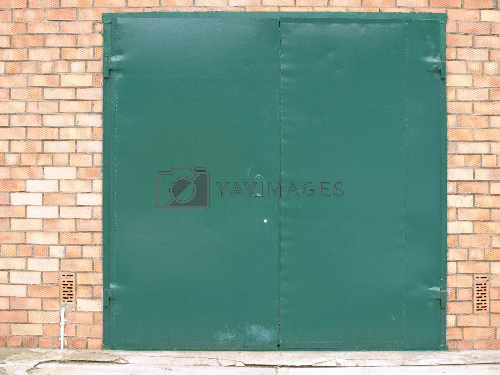 Green metalic door in the bicks wall