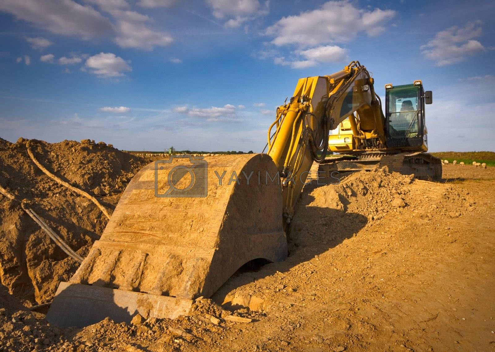 Dirty yellow excavator photographed in a sunny summer day