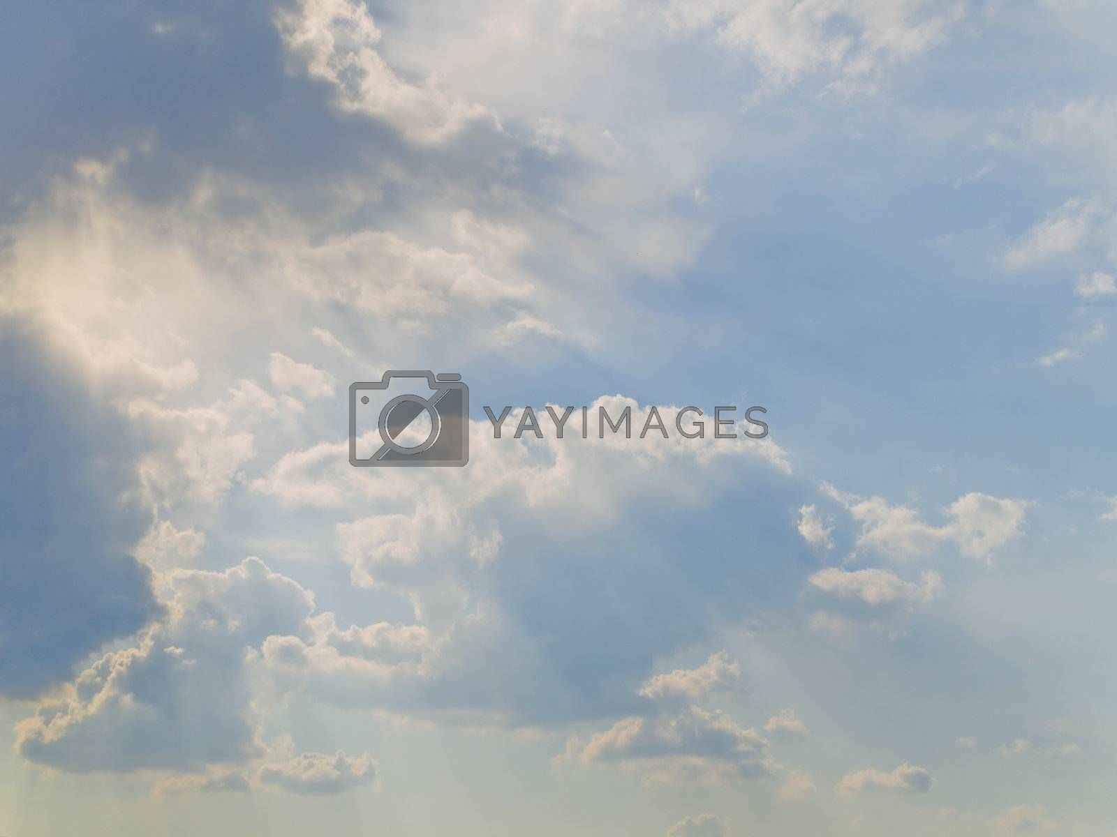Clouds at the blue sky with sun shaft
