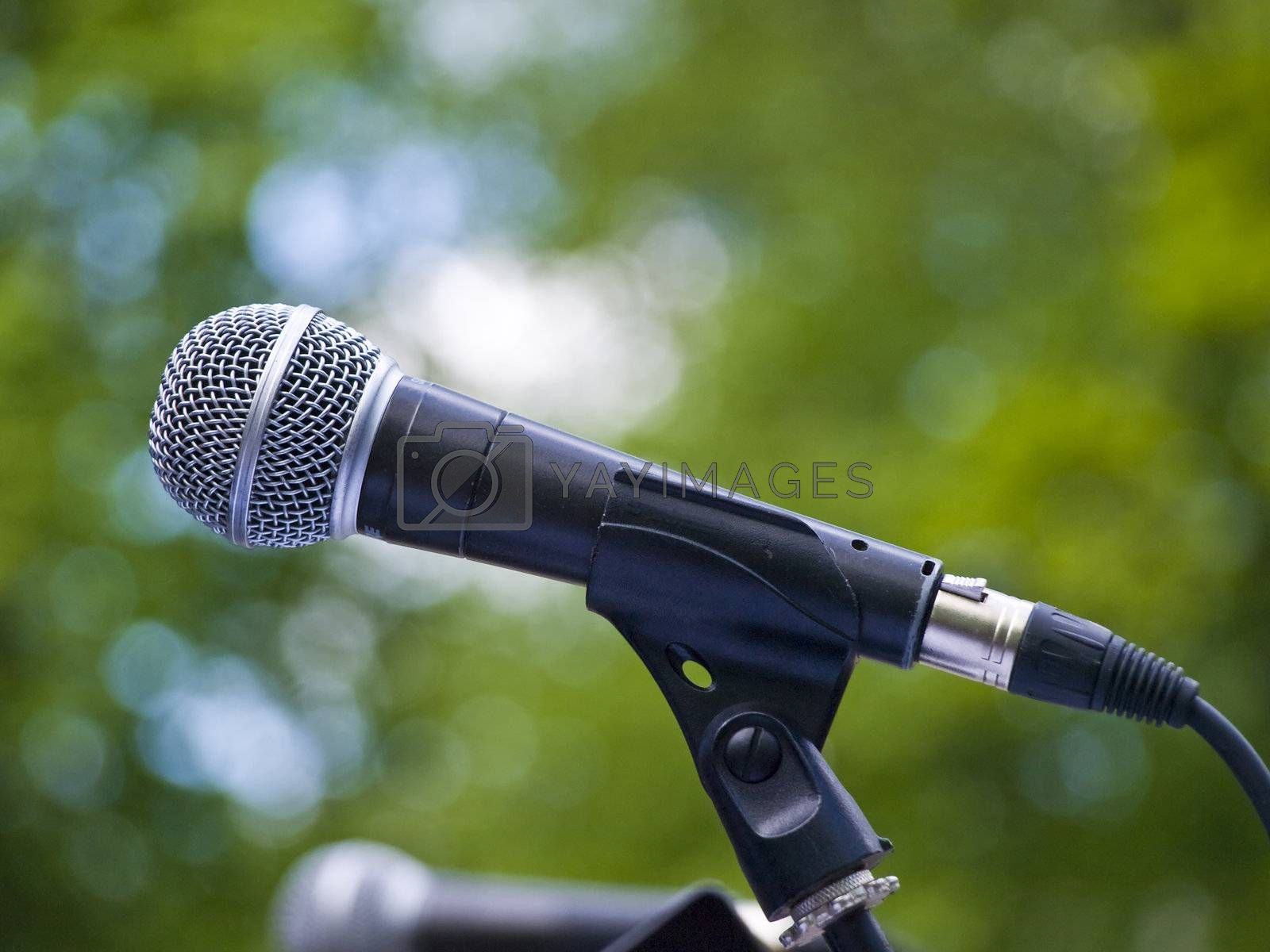 Single microphone against the green leaves background