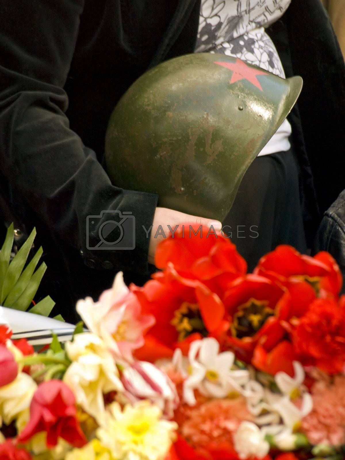 Old metal russian oldier hat in hands near the flowers