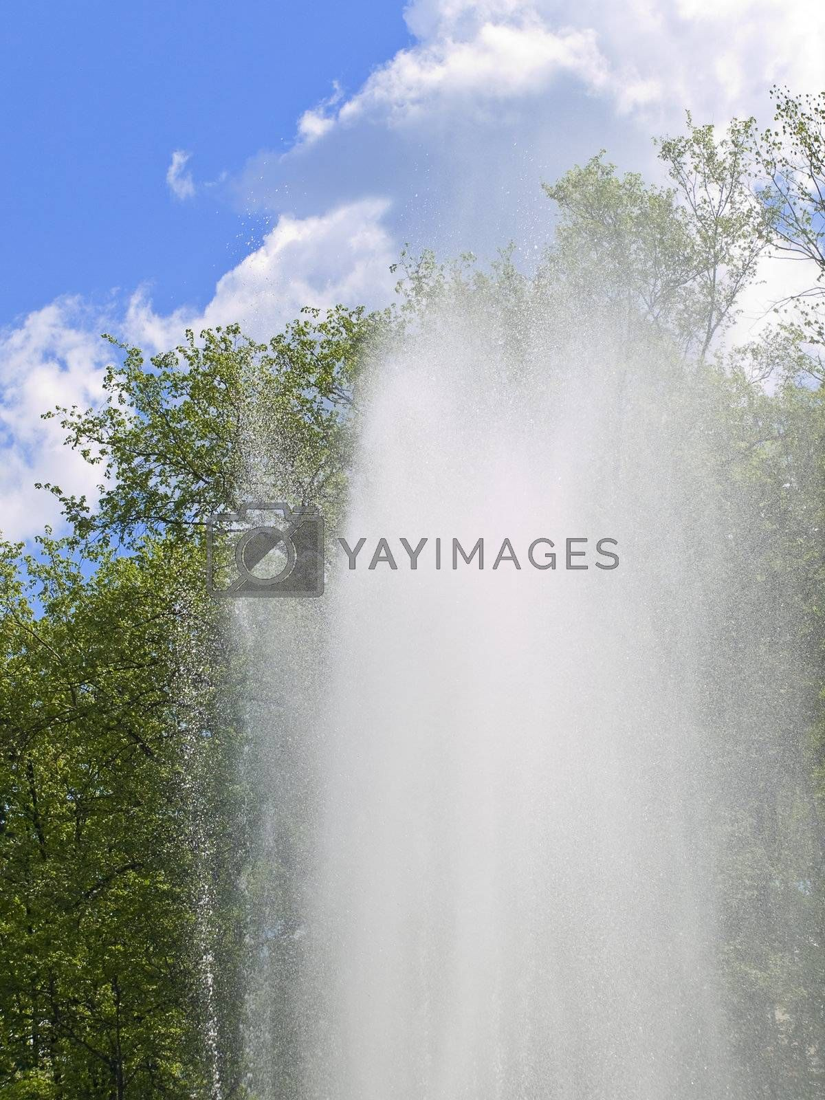 fountain against the blue sky with clouds and green trees