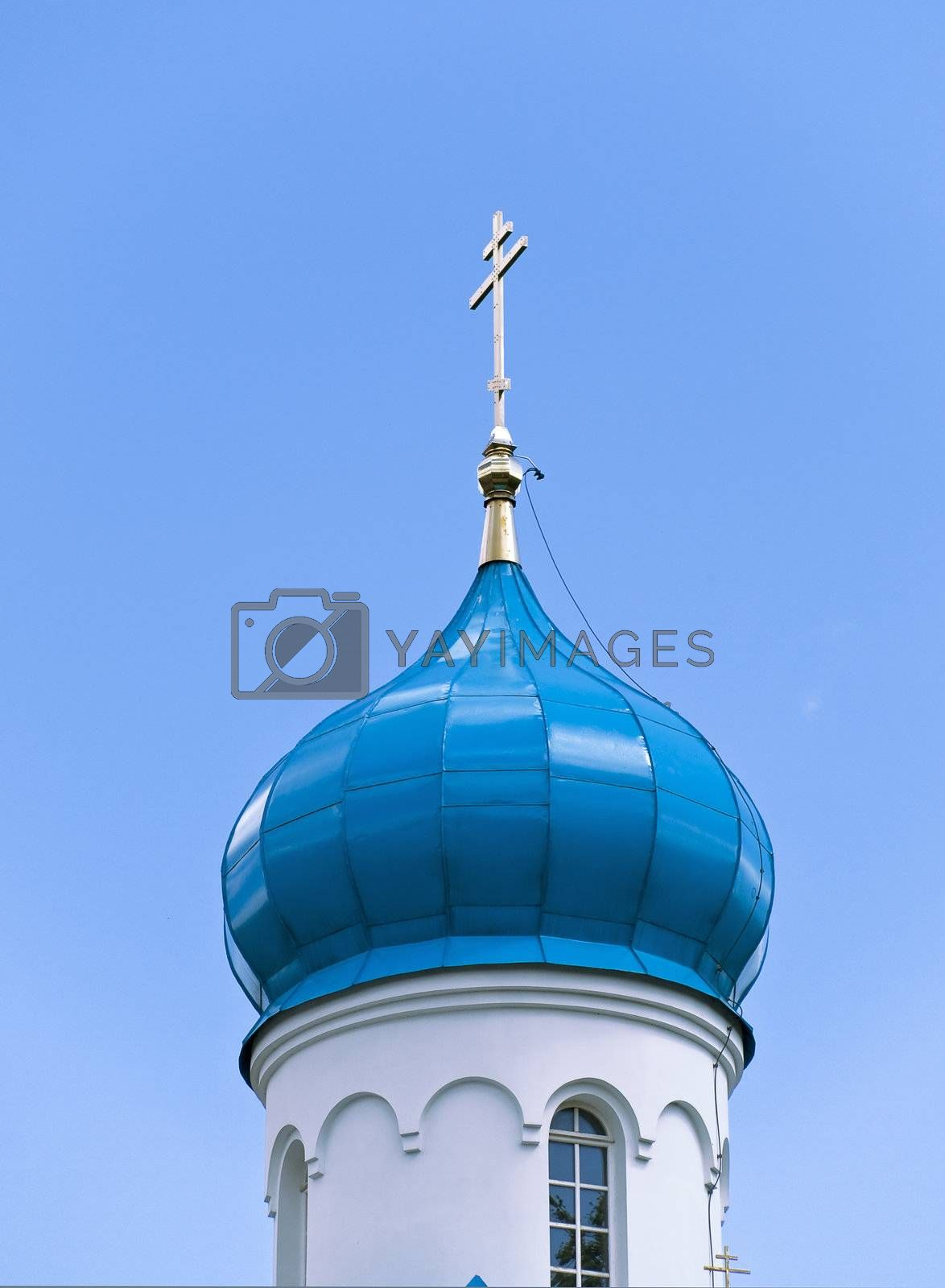 Blue cupola of the church with gold cross against the blue sky