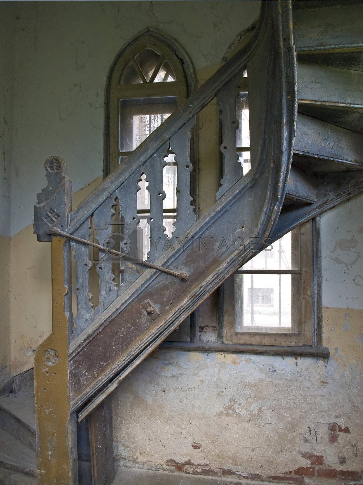 Old spiral stairs in tower wih arch windows