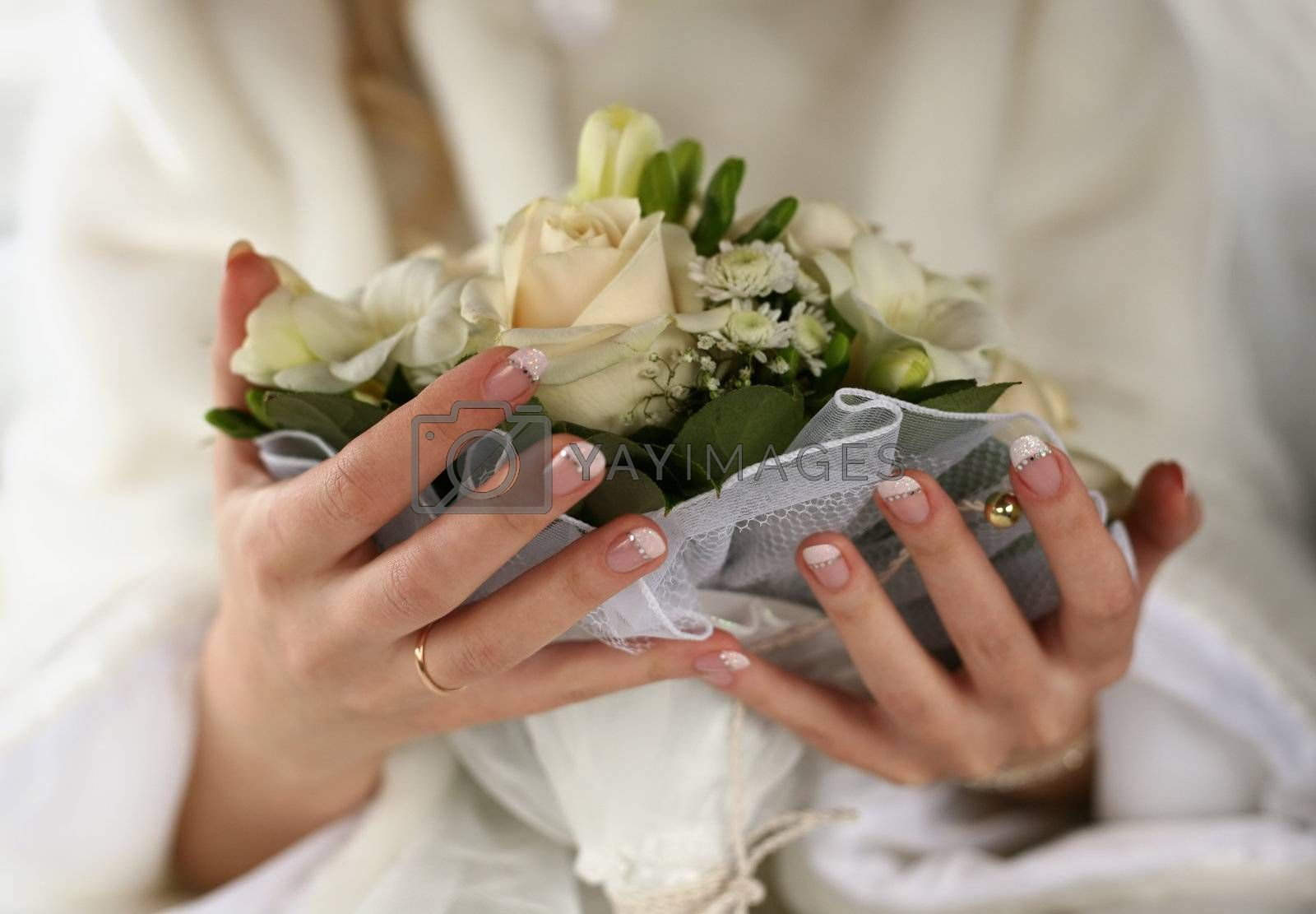 Hands of the bride with a ring and  bouquet