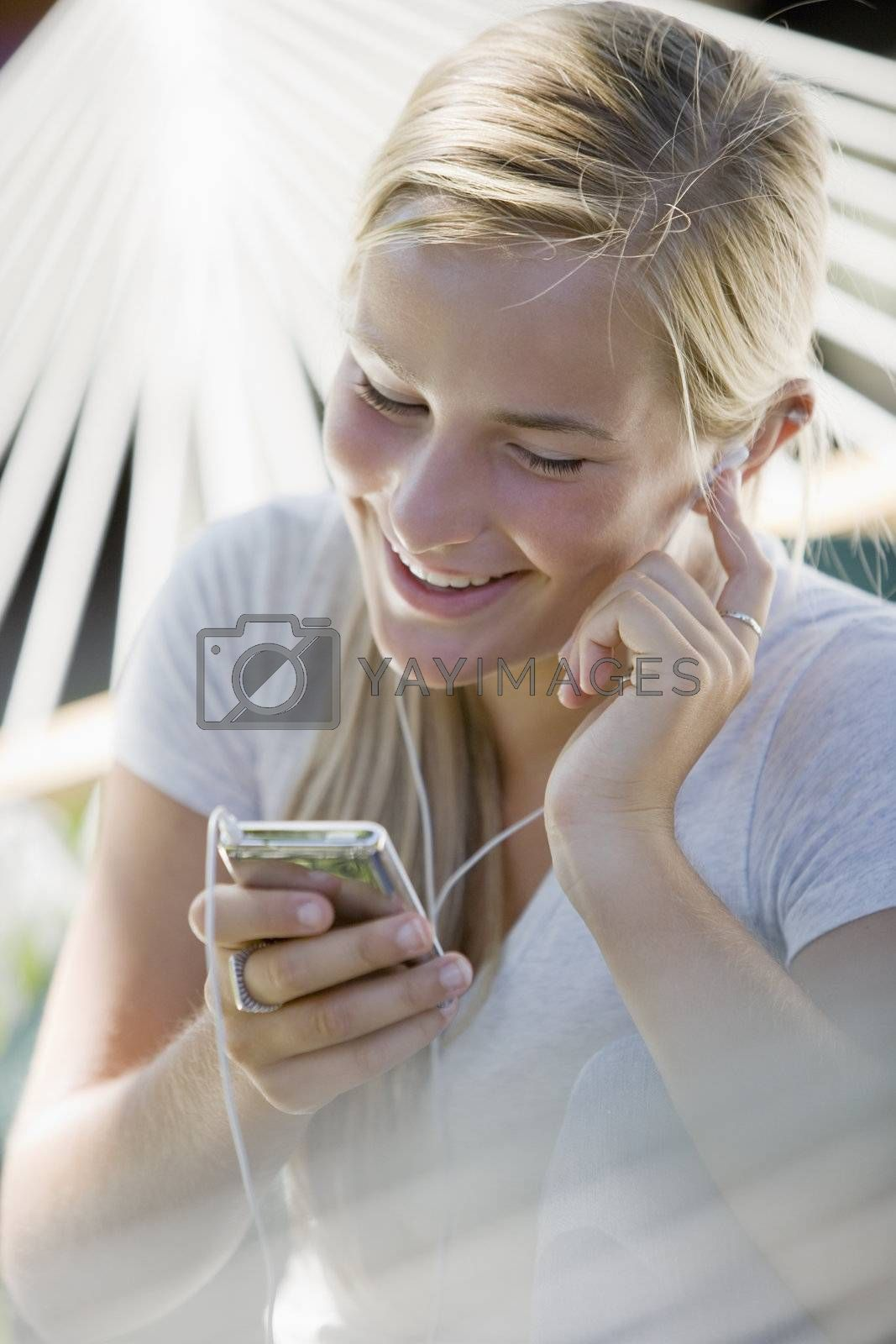 Teenager with earbuds listening to MP3 player