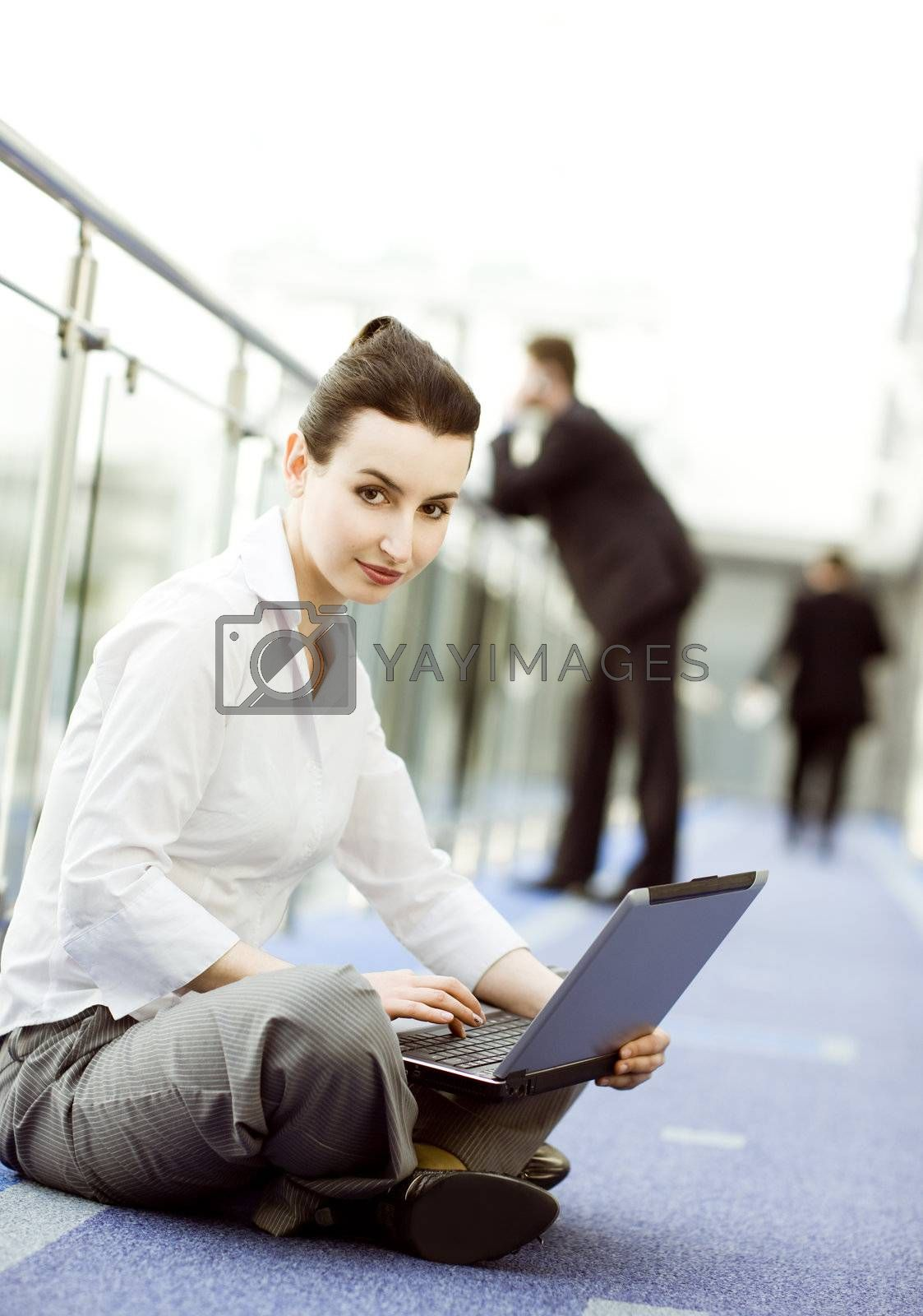 Businesswoman is sitting on the floor with notebook on her lap