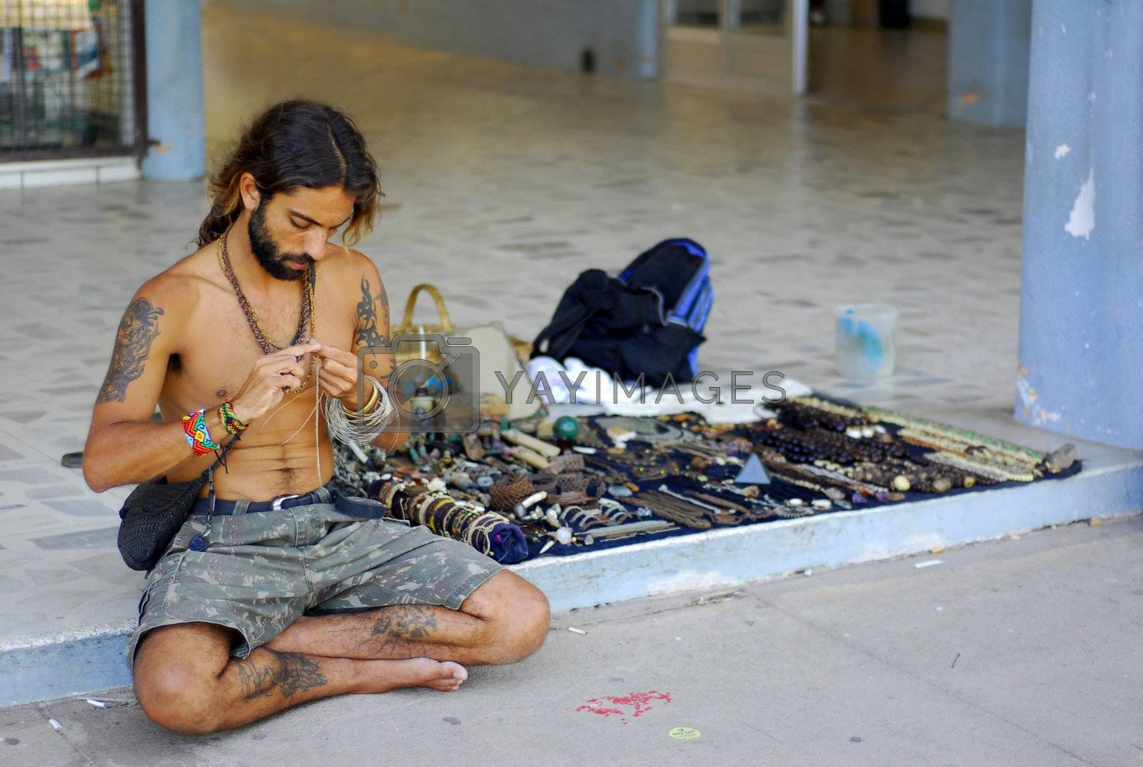 A hippie working on his crafts sitting on the curb