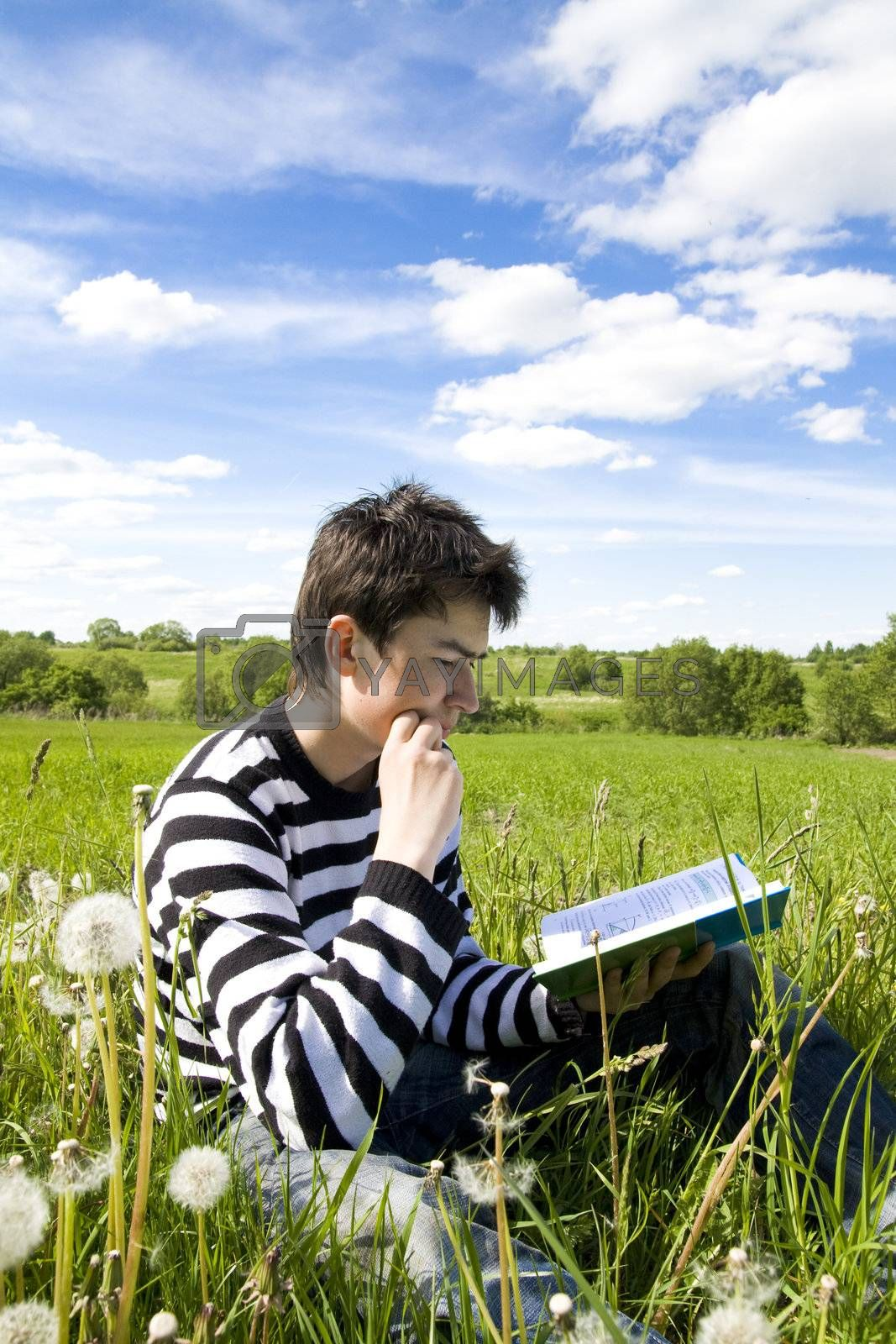 Boy reading a book on the grass. Time before examination