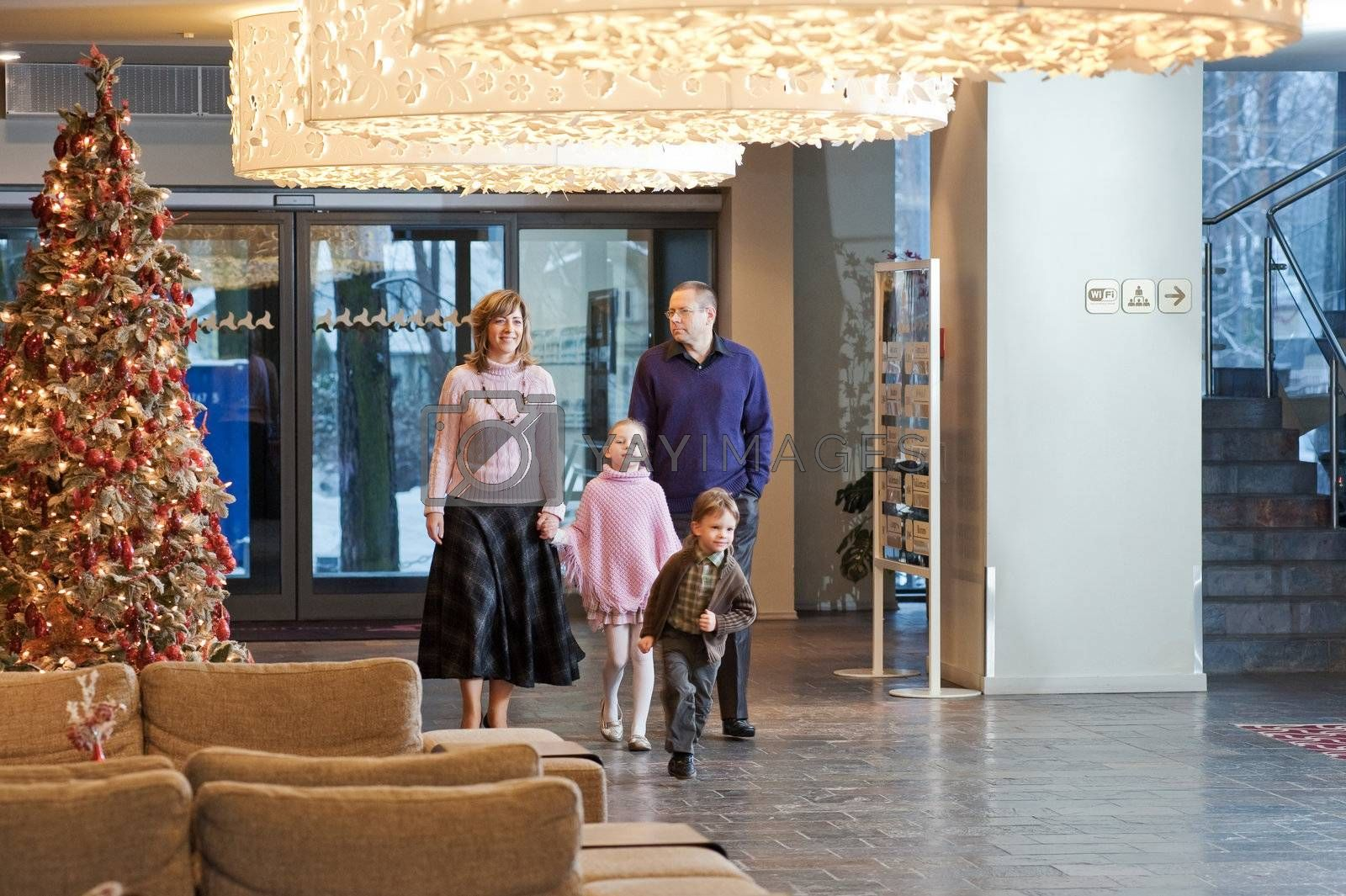 Happy family walking at foyer in the modern hotel