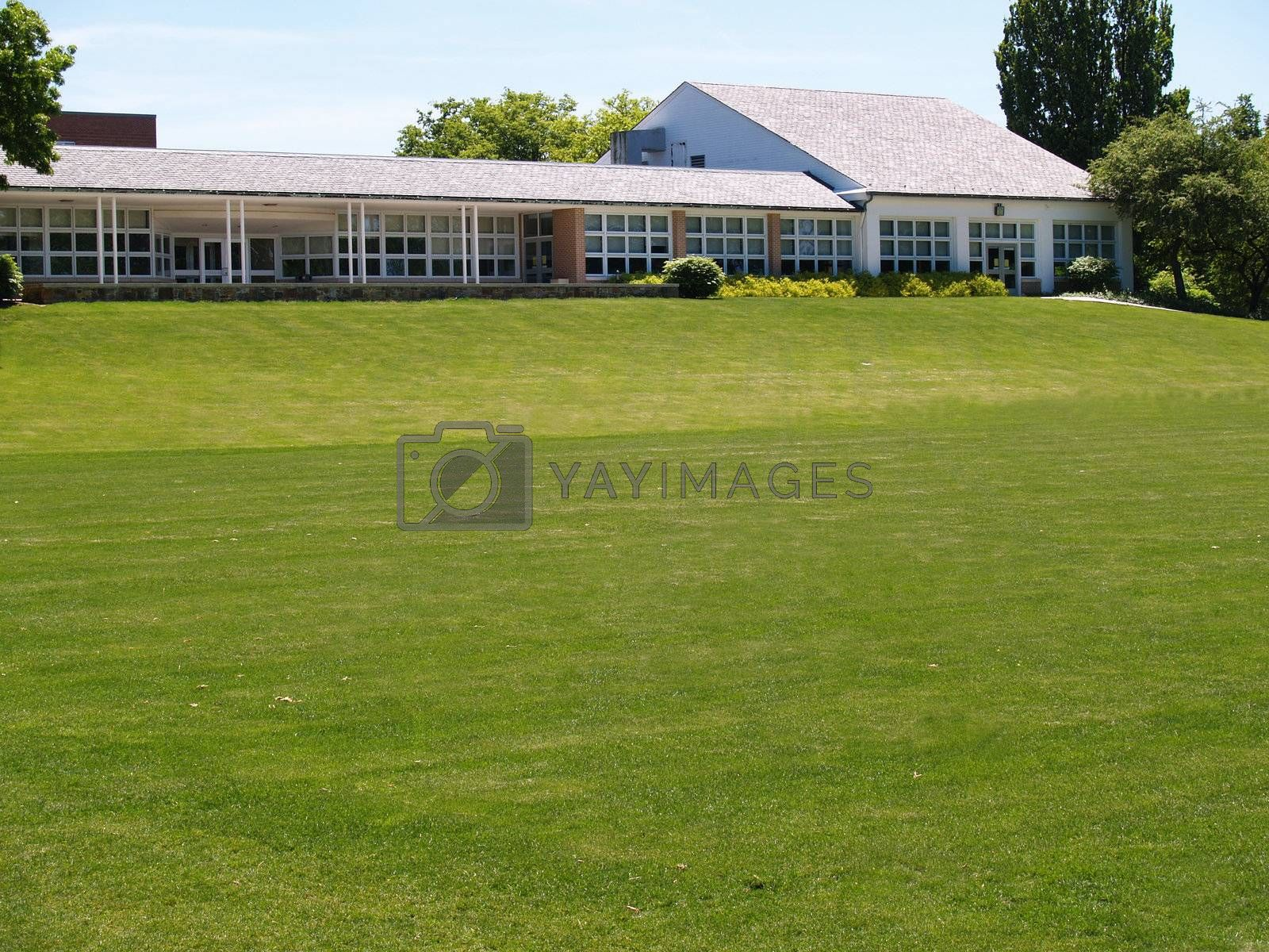 a large grass area by a building with many windows