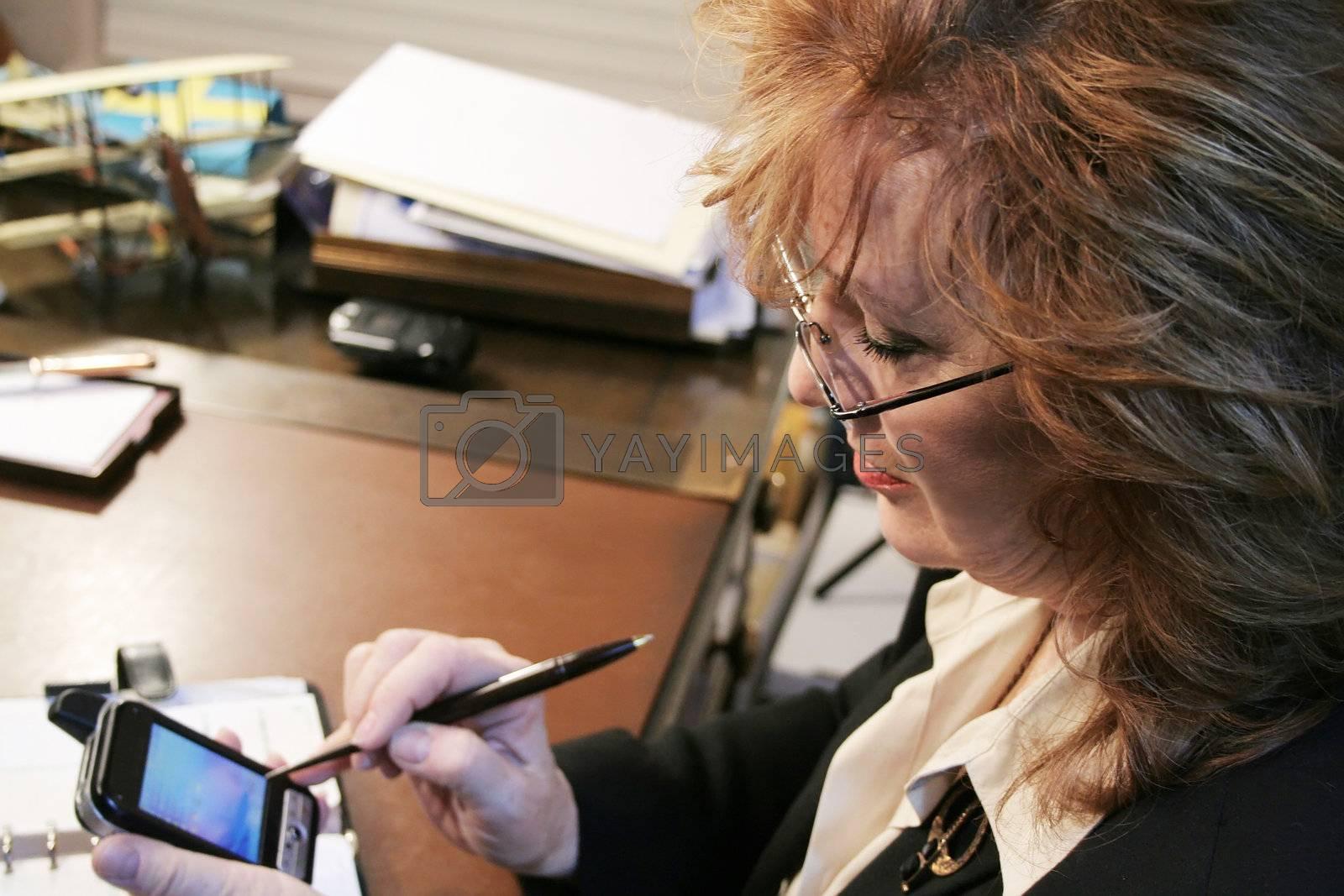 Executive woman typing on PDA screen