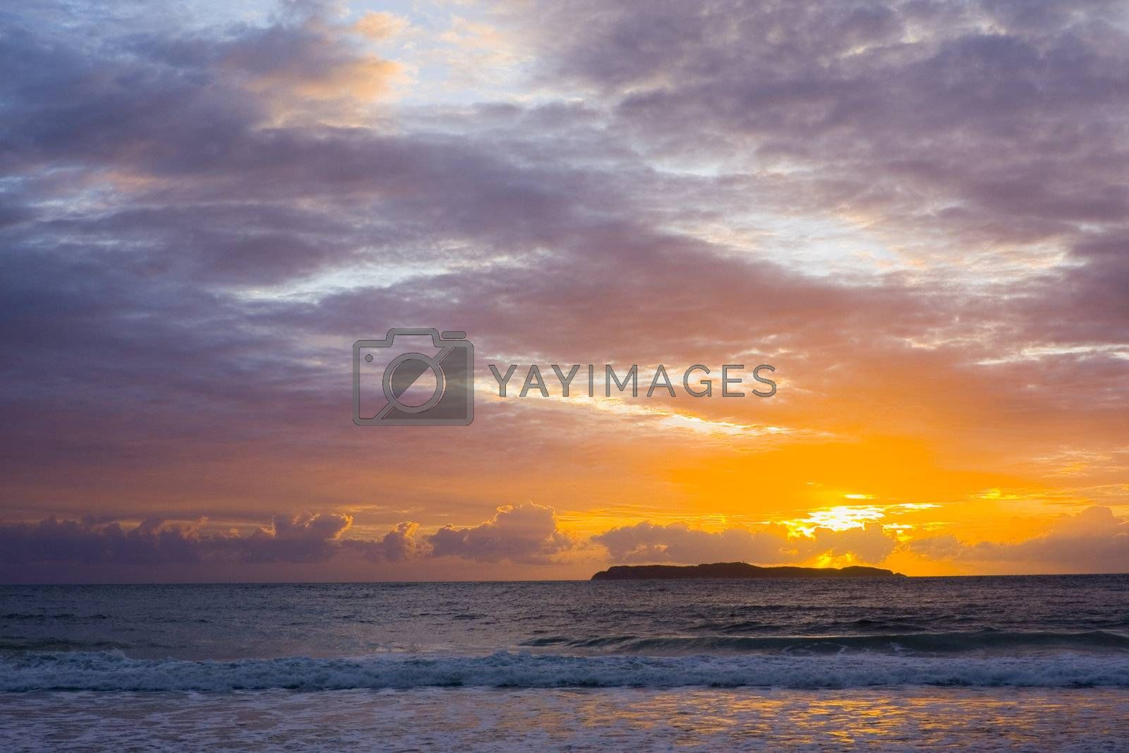 Dramatic sunrise over the sea with an island in the background