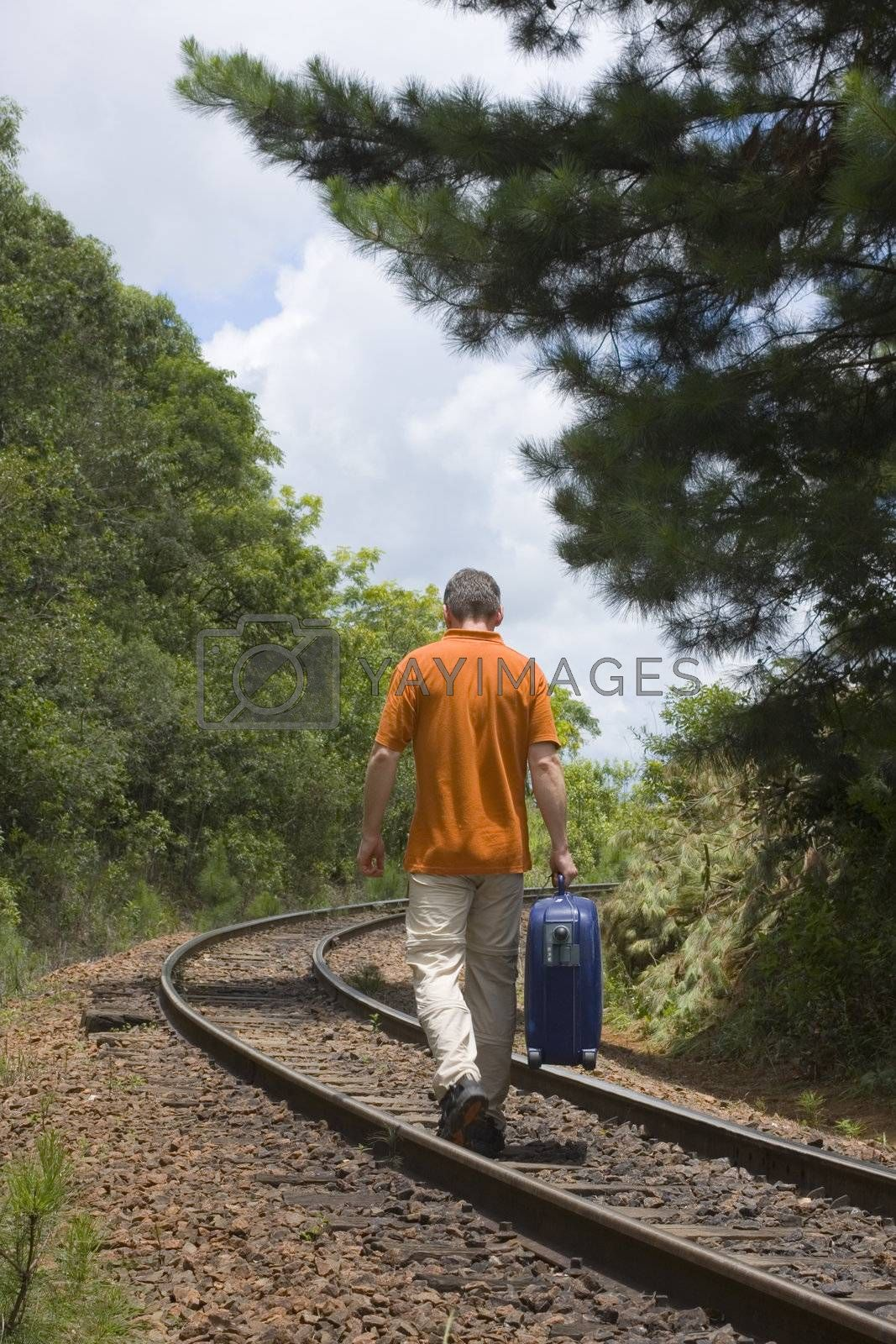 Man walking on a railroad with his suitcase