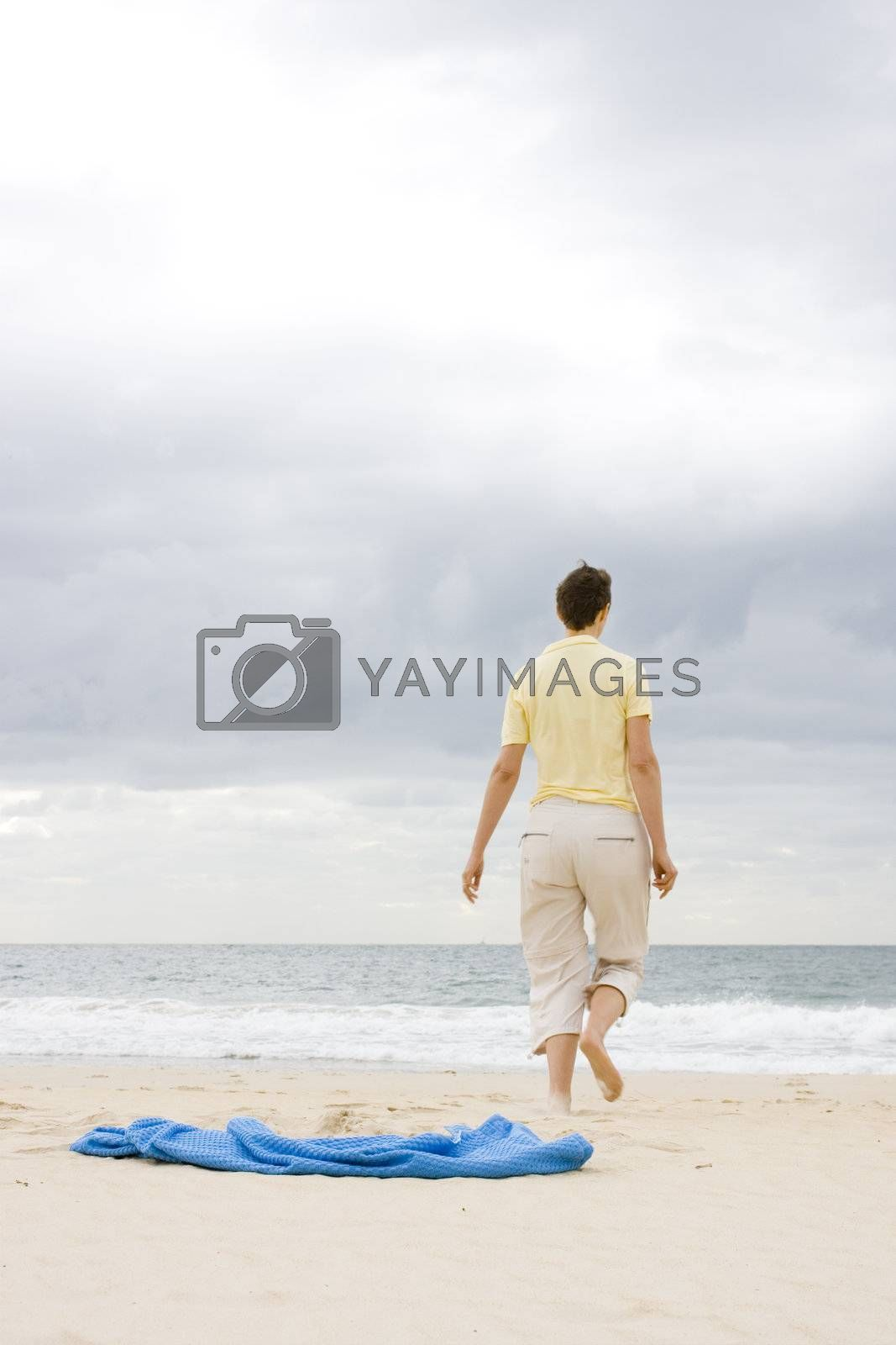 Woman walking on a beach. Focus on the towel in the foreground