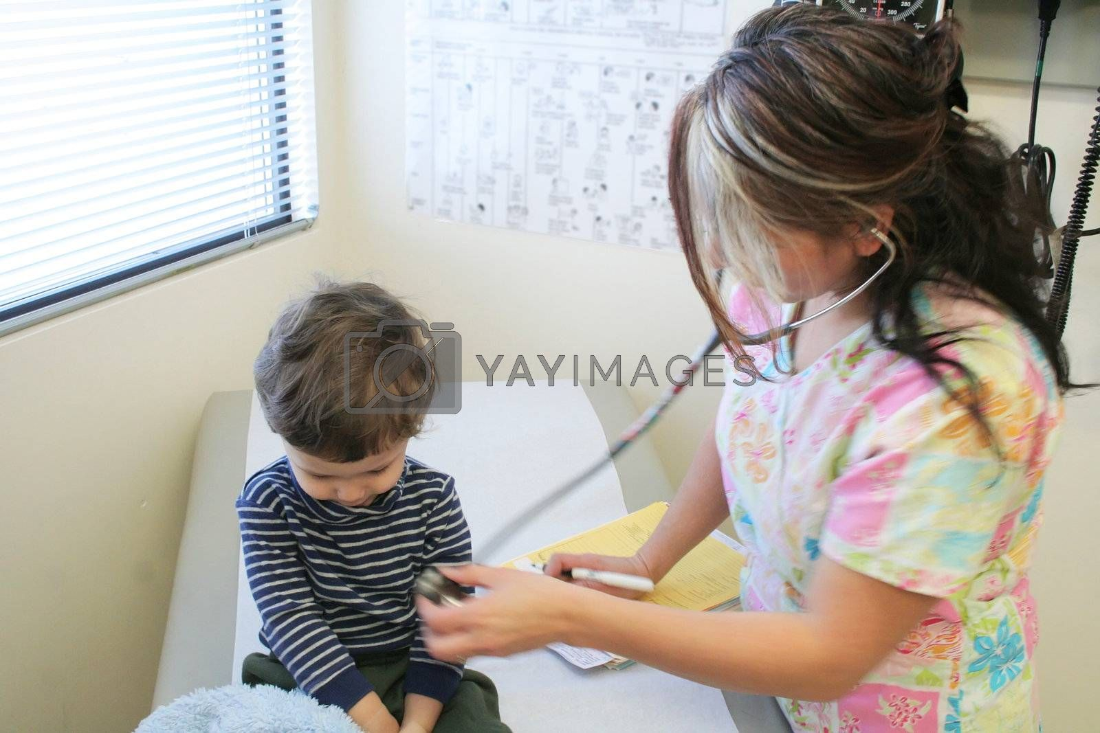 Young child getting a checkup from a nurse