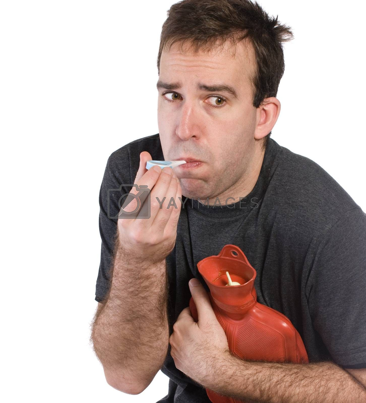 Closeup of a sick man taking his temperature and holding a hot water bottle to his stomach, isolated against a white background