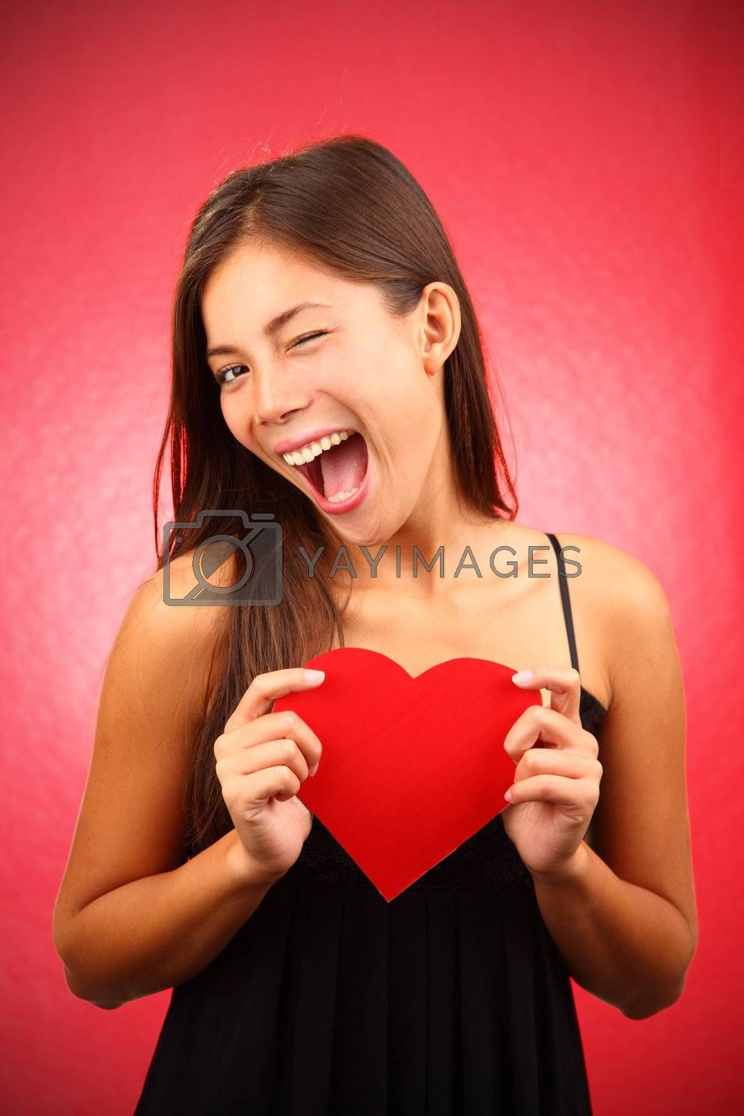 Woman holding Valentines Day heart sign. Beautiful mixed race chinese / caucasian model.