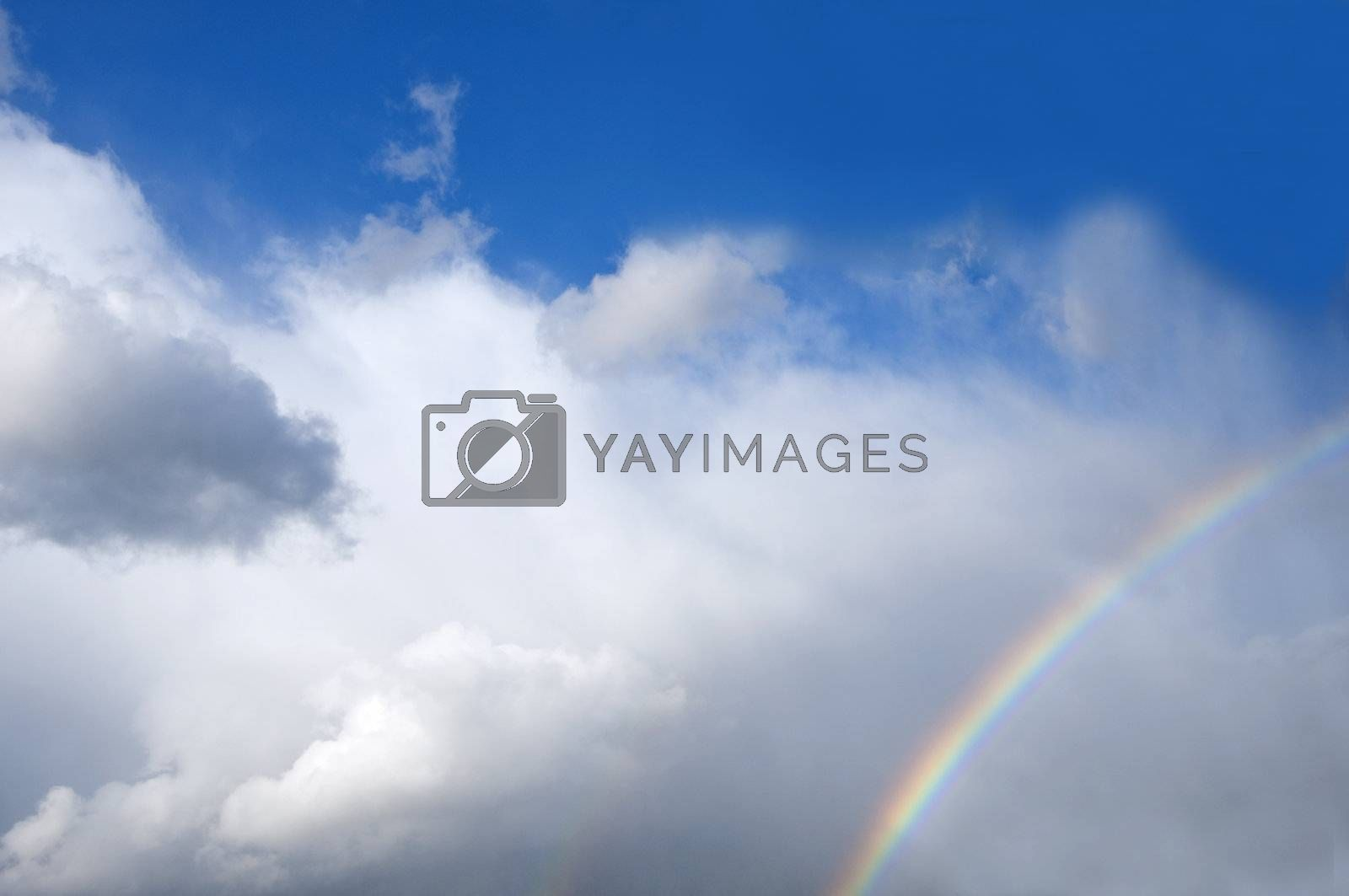 two rainbows in the sky filled with white clouds
