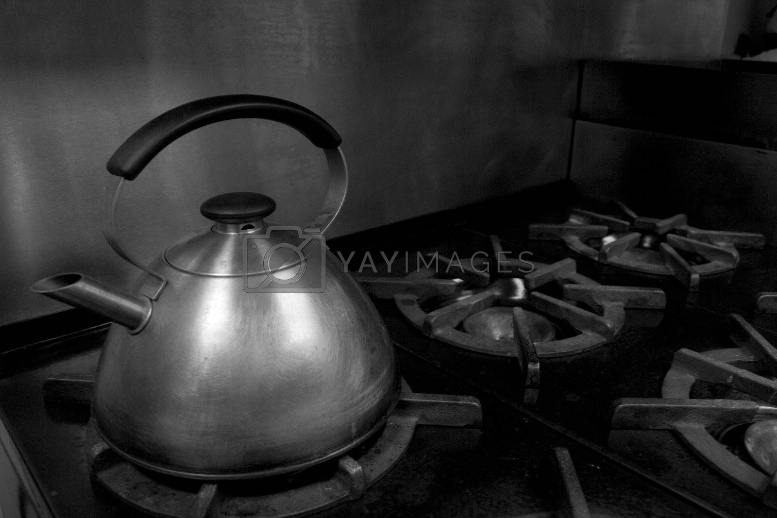 A water kettle on an old iron stovetop.