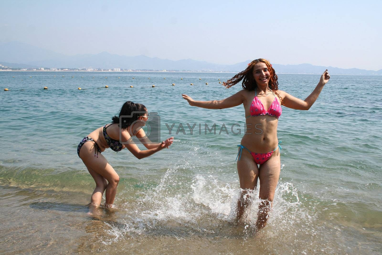 Portrait of 2 beautiful woman playing on beach and waves