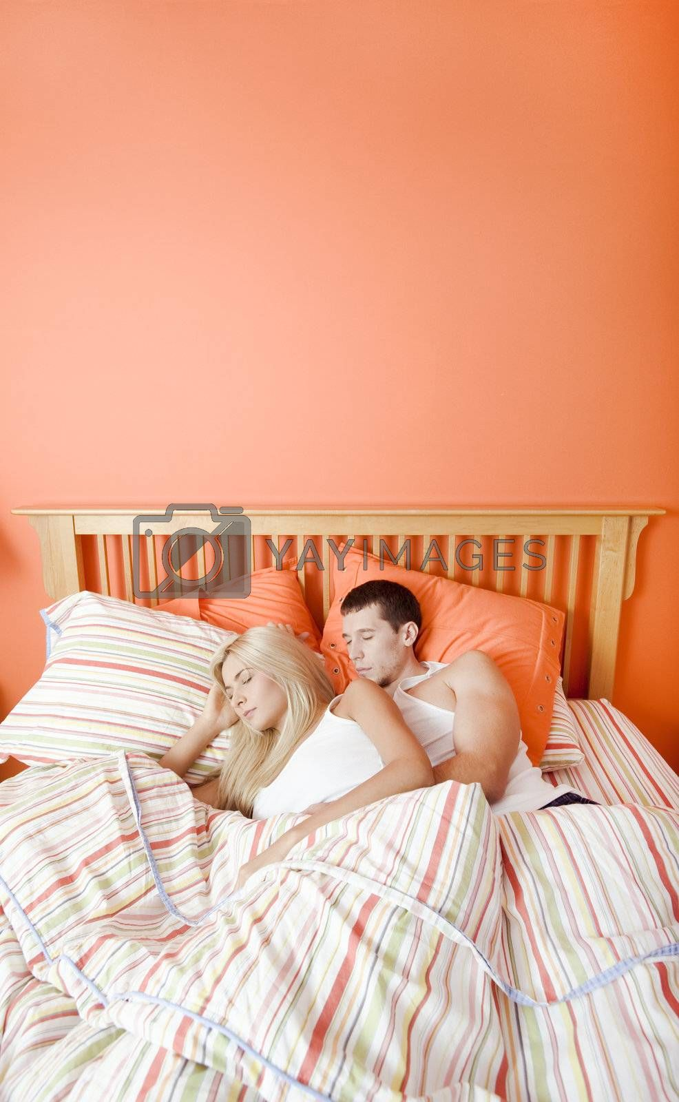 High angle view of young couple sleeping closely together under a striped bedspread. Vertical shot.
