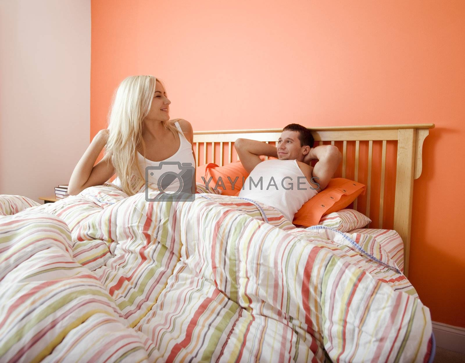 Young couple wake up in bed under a striped bedspread. Horizontal shot.