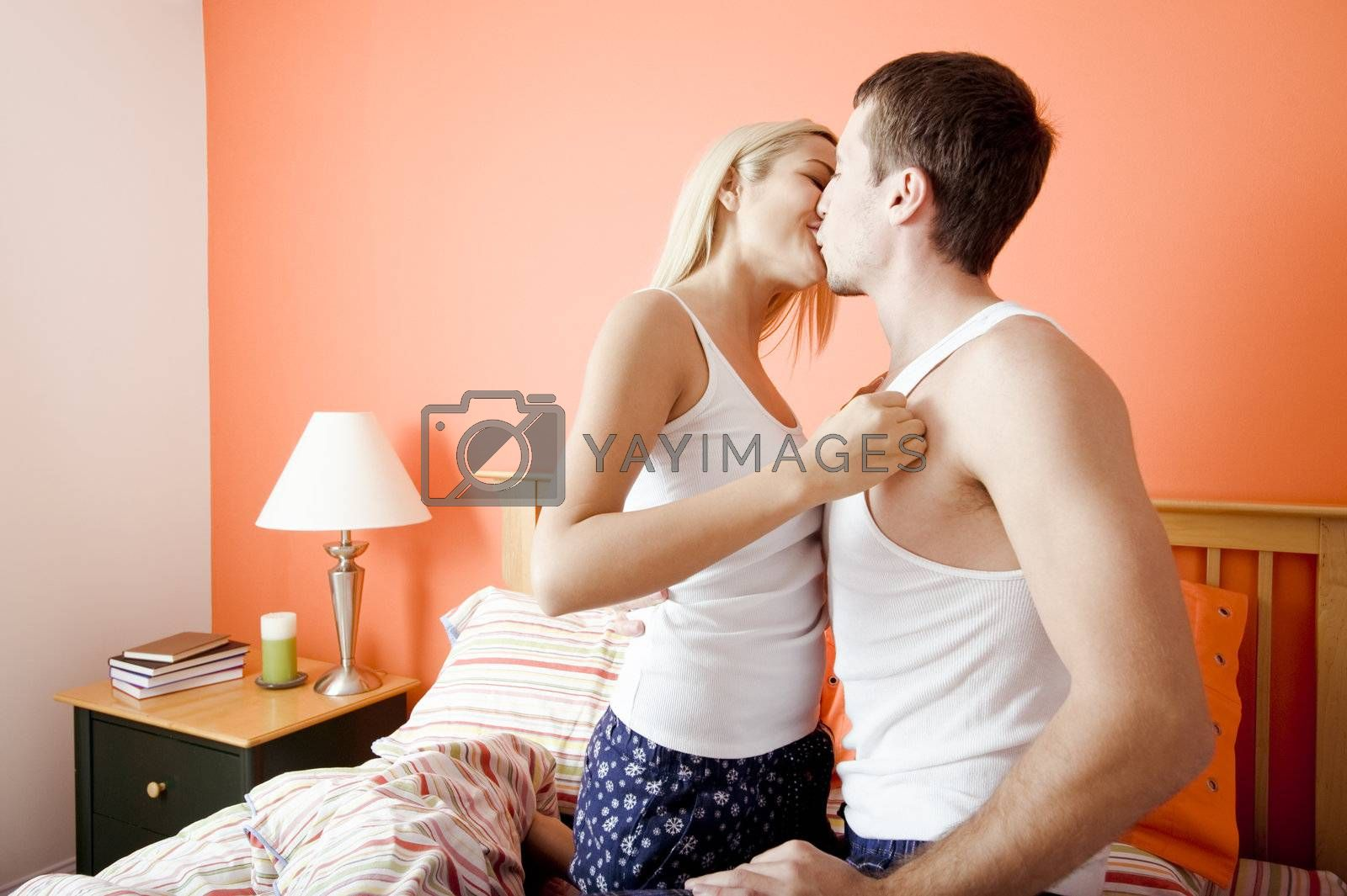 Young couple wearing white tank tops kiss passionately while kneeling on bed. Horizontal shot.