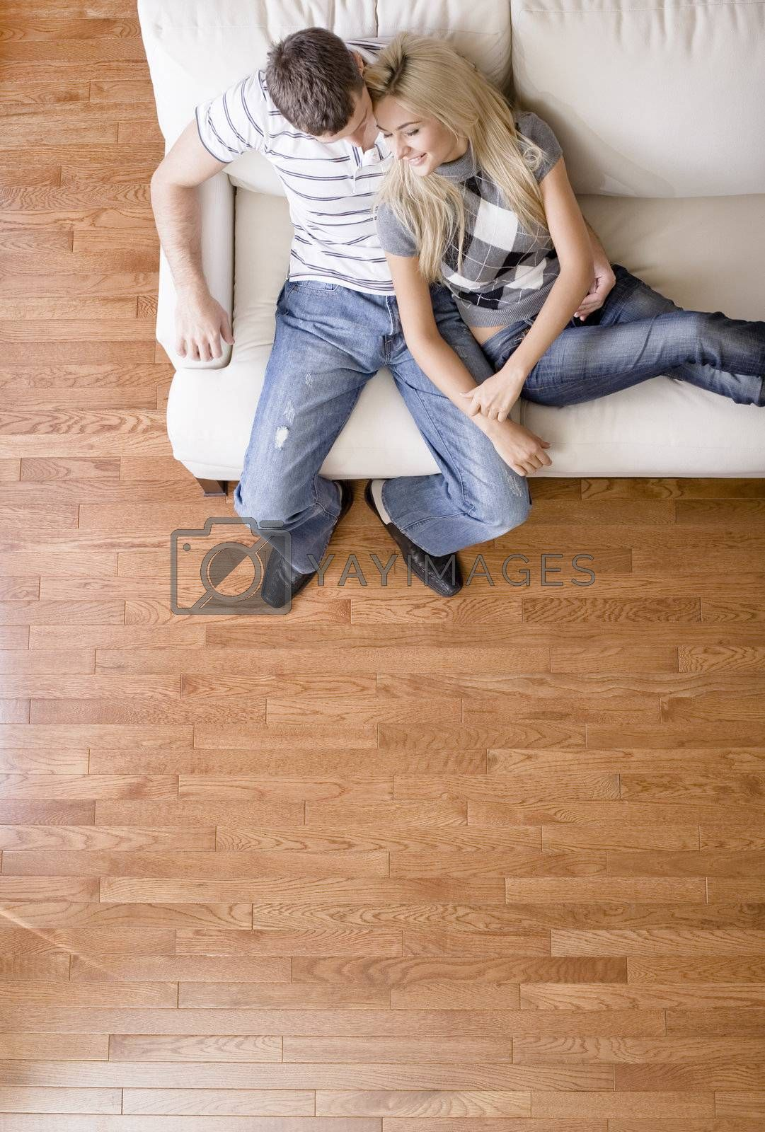 Cropped overhead view of affectionate couple sitting together on white love seat. Vertical format.