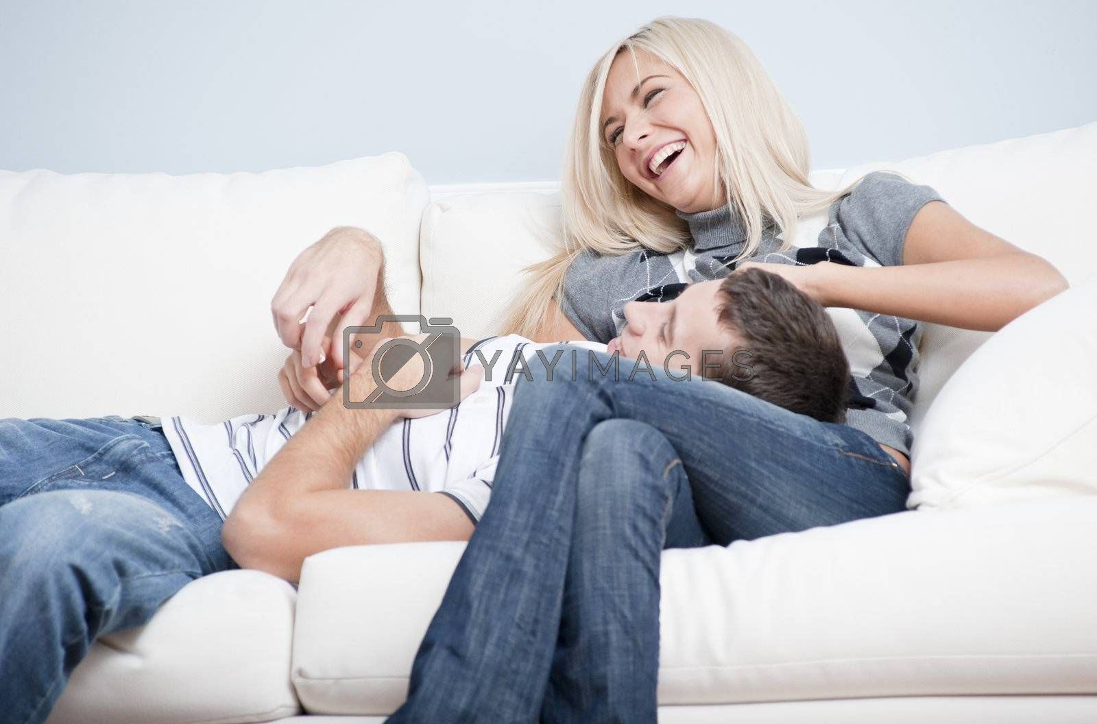 Laughing couple relaxing on couch, with man lying with his head in the woman's lap. Horizontal format.