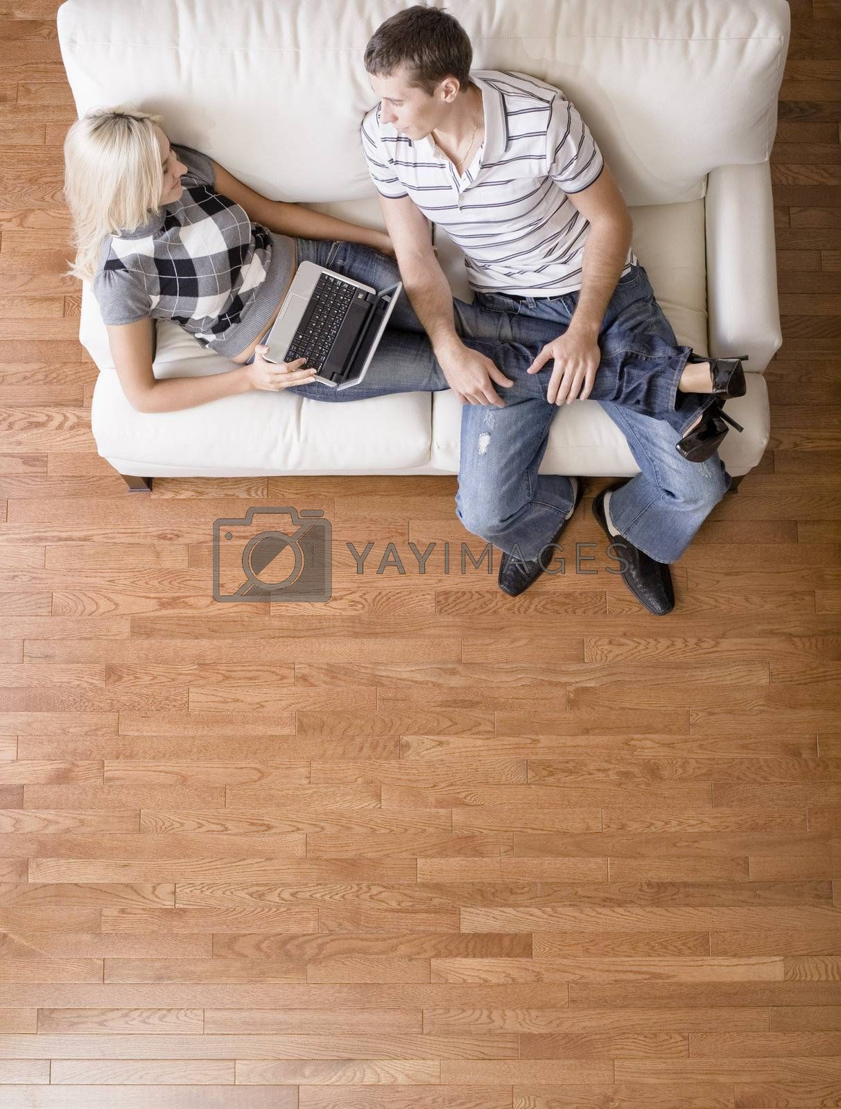 Full length overhead view of couple relaxing together on white couch, with woman using laptop and stretching out with her legs in the man's lap. Vertical format.