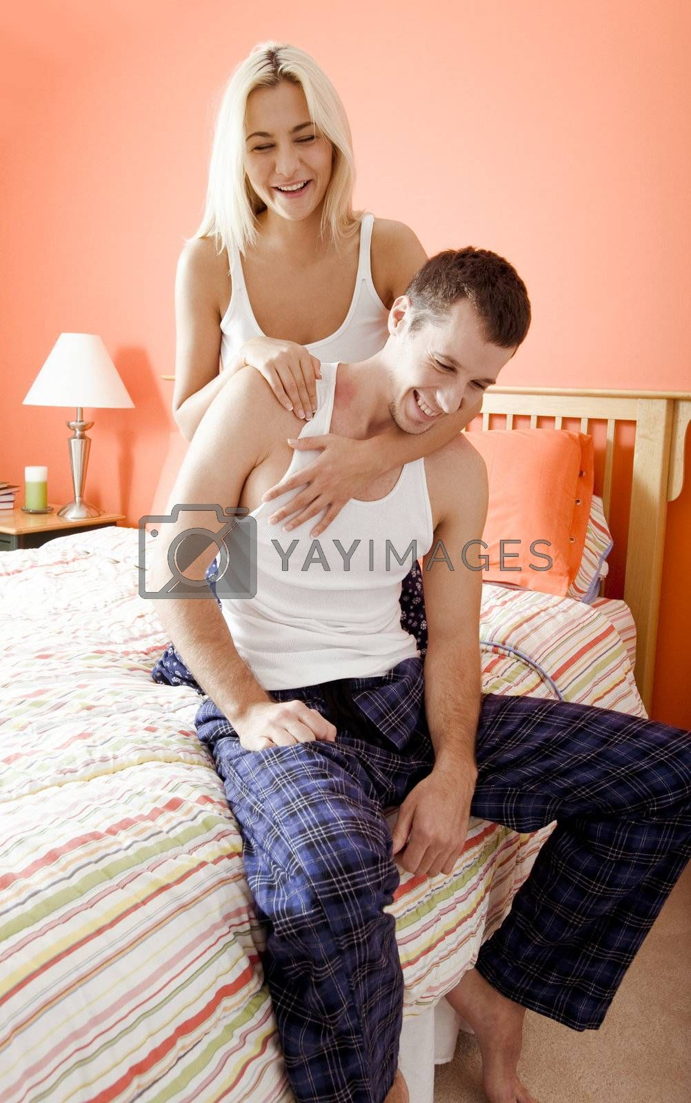 Affectionate couple in pajamas, laughing and relaxing in their bedroom. Vertical format.