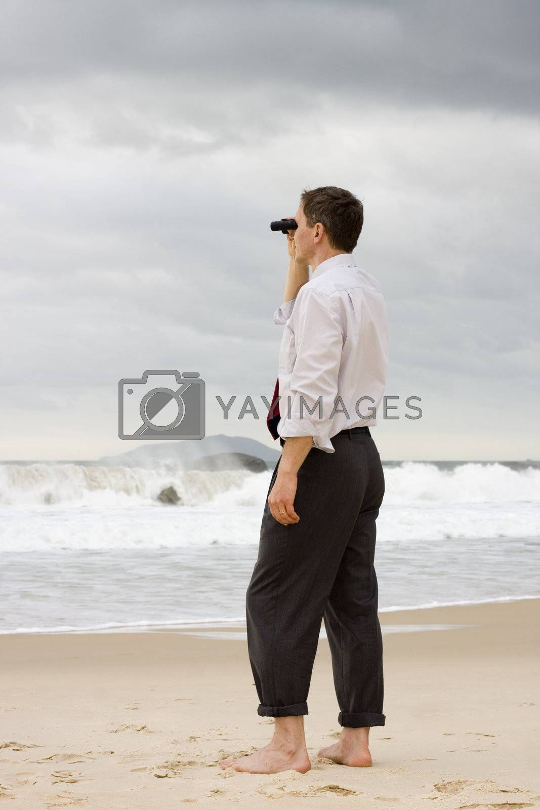 Businessman on a beach searching with binoculars by ArtmannWitte