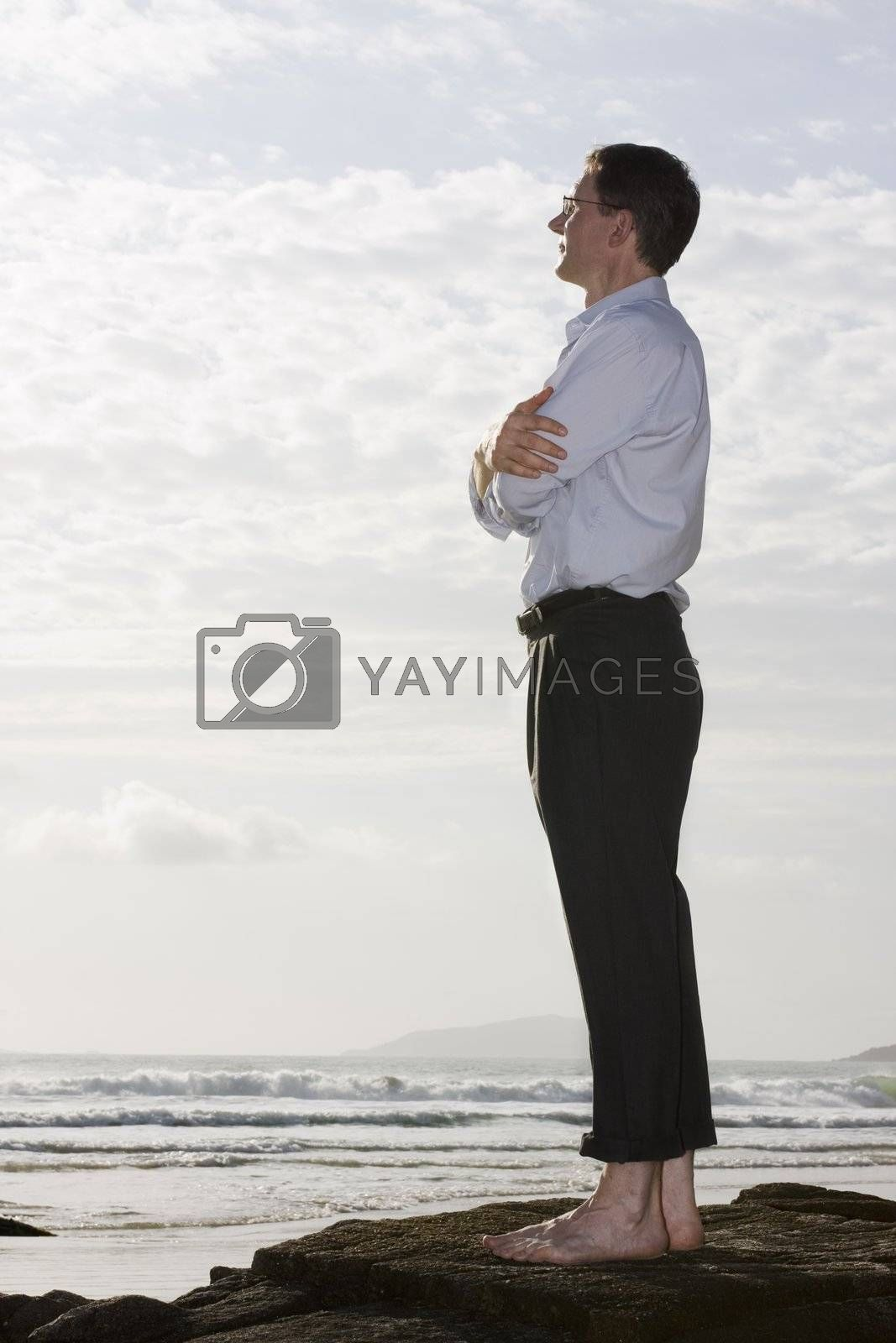 Businessman enjoying the sun on a rock on a beach