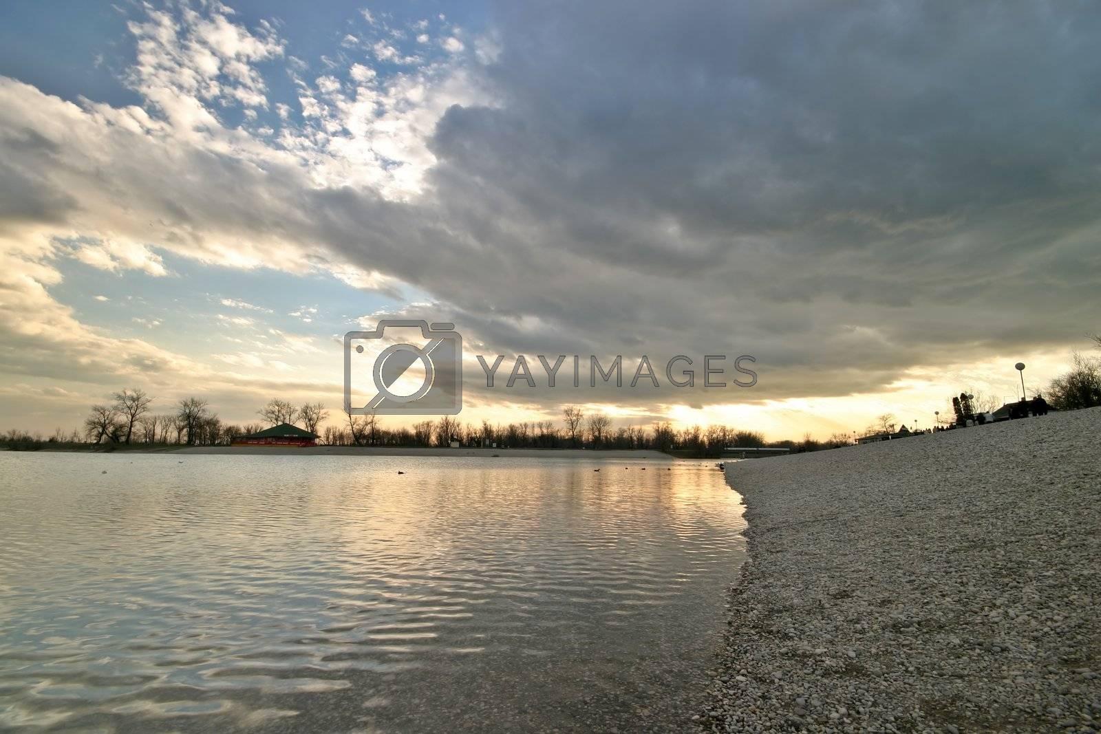 Cloud, lake and pebble coast sunset