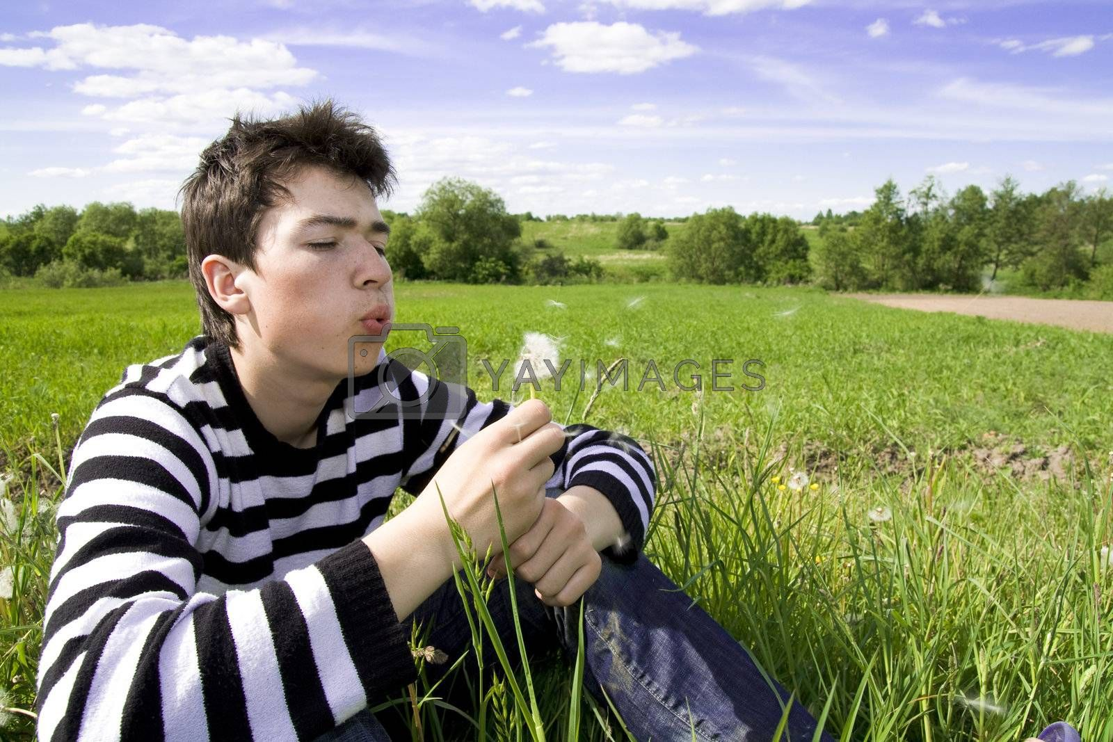 Portrait of teenager blowing a dandelion