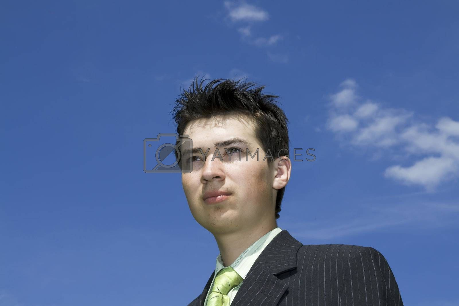 Portrait of happy young man on blue sky background; copy space