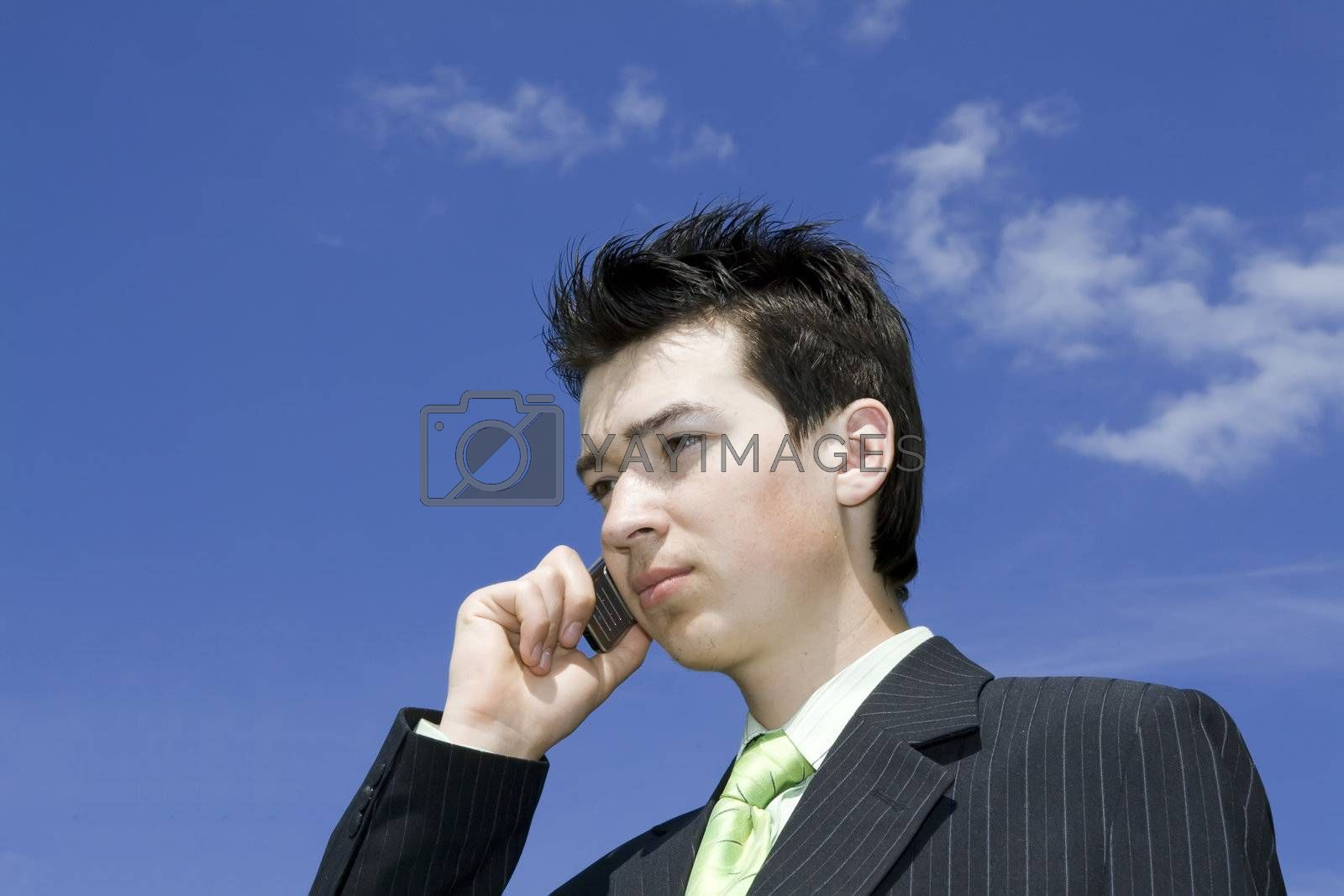 Businessman talking with mobile against blue sky background. Copyspace