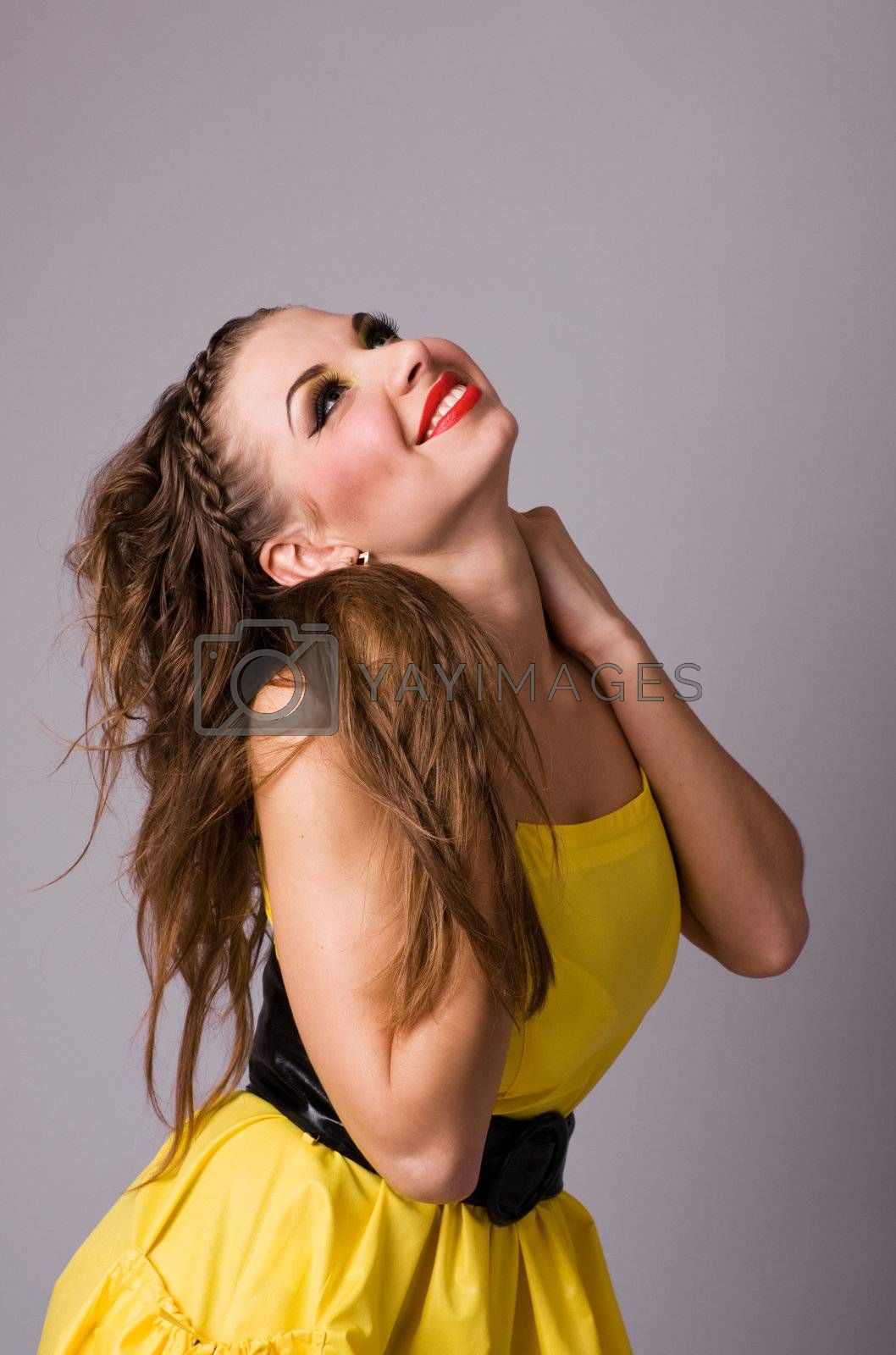 Satisfied attractive young woman in yellow