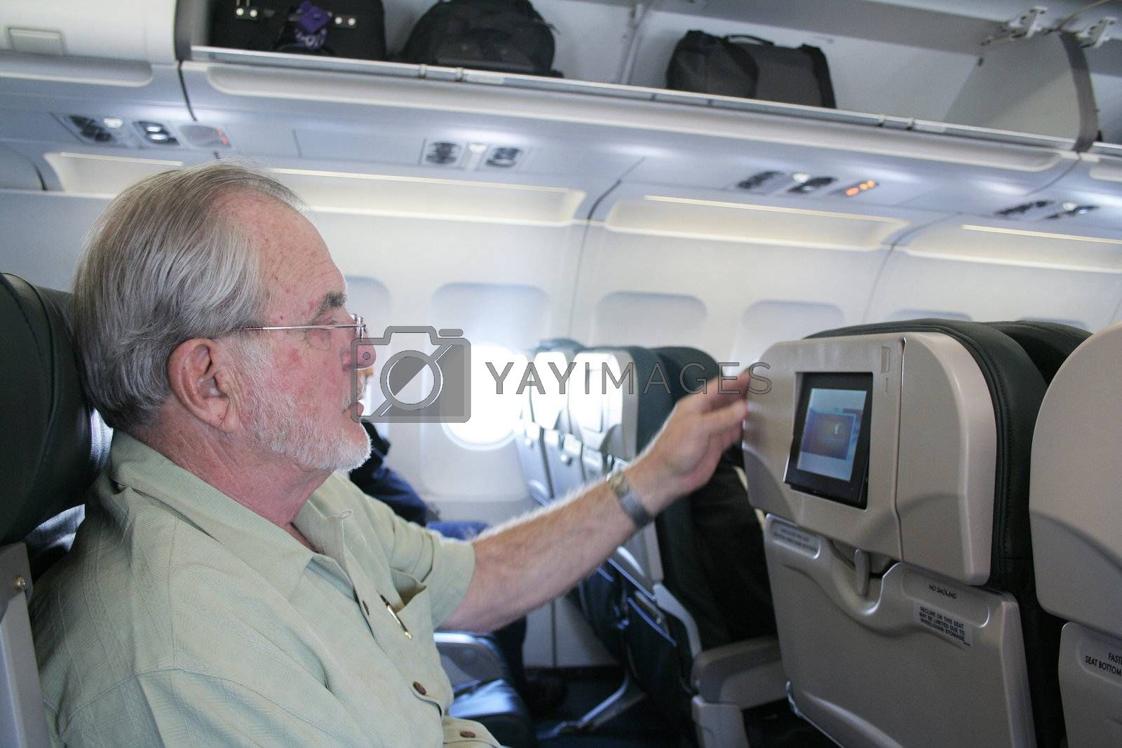 Man on airplane looking at inflight tv