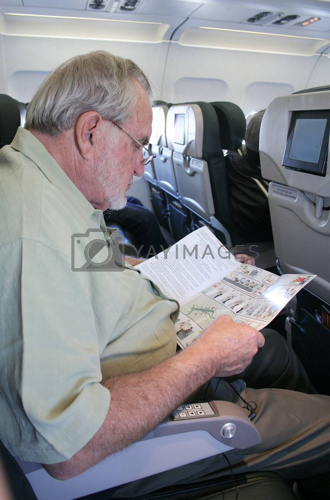 Man on airplane reading safety instructions