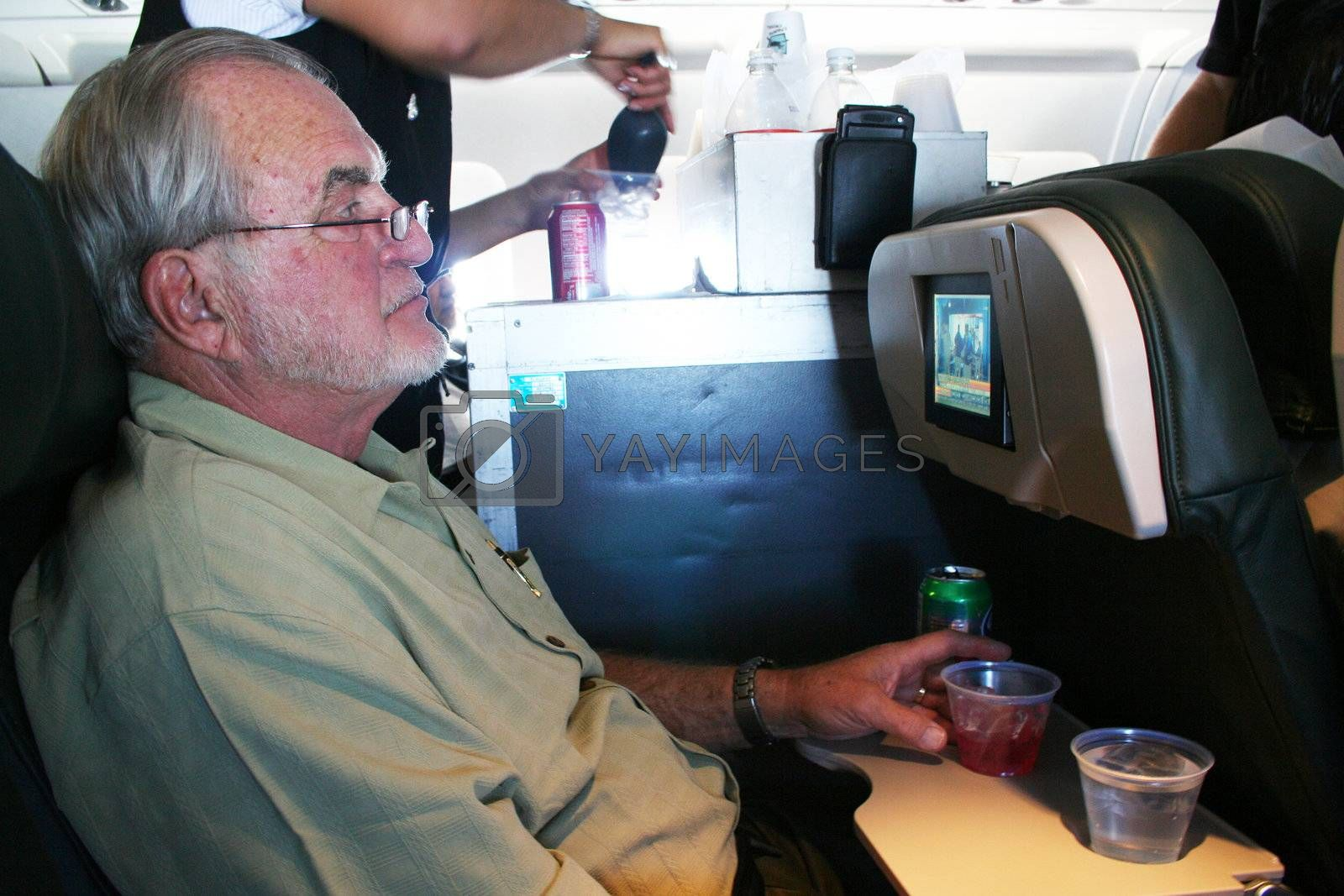 Man on airplane with stuartess serving drinks
