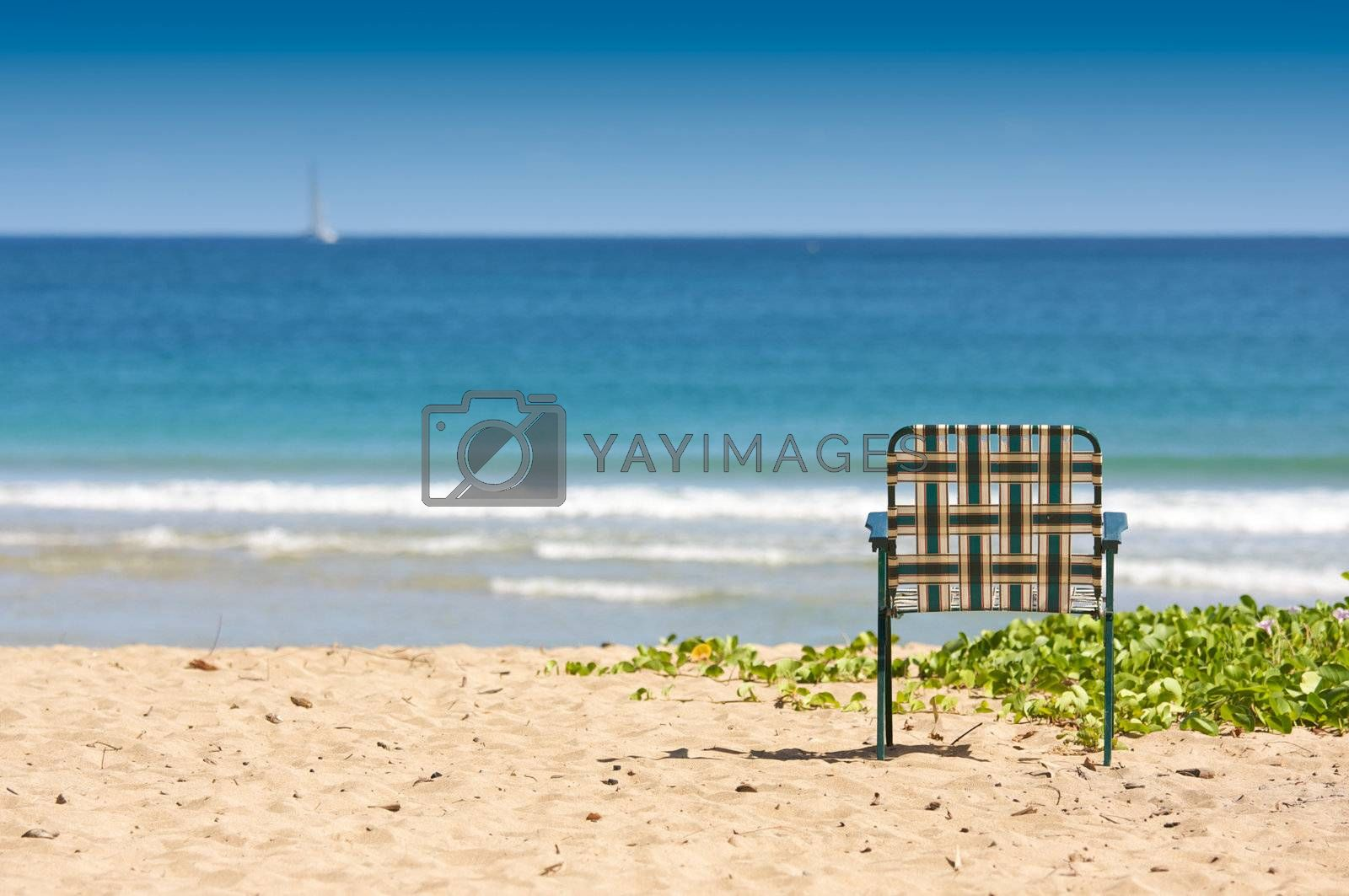 Chair sits on an inviting tropical shore.