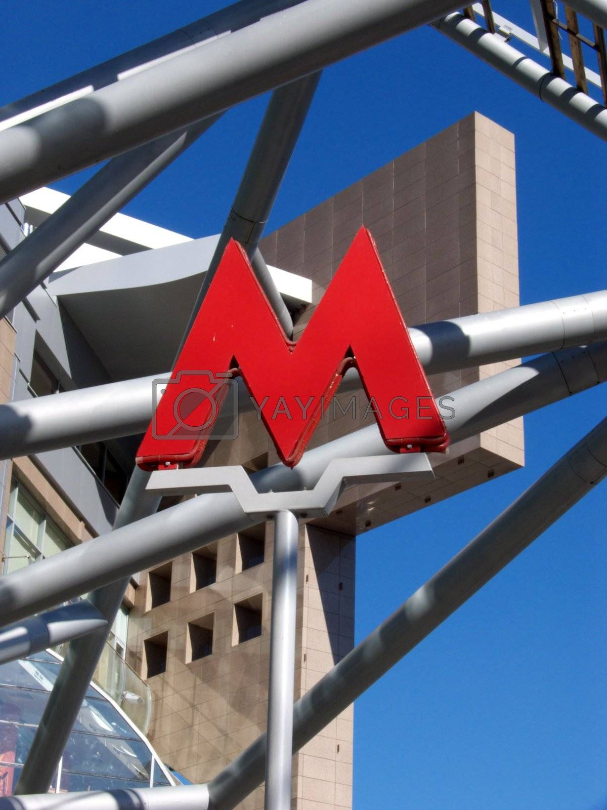 The greater red letter M on a background of a modern building.